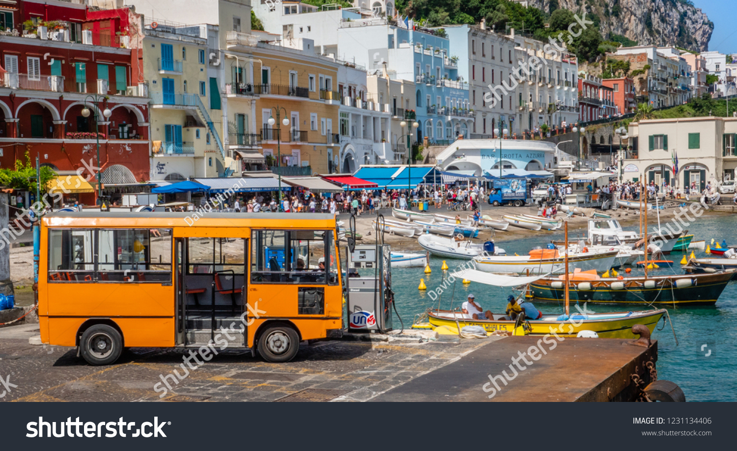 Capri, Italy - June 11, 2018: An orange shuttle bus fills up at a gas station on the dock at Marina Grande, with boats in the marina and colorful buildings along the coast.