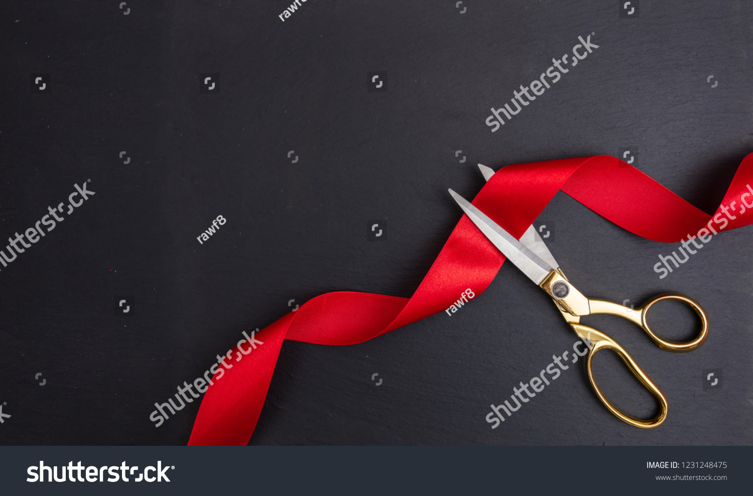 Grand opening. Top view of gold scissors cutting red silk ribbon against black background, copy space #1231248475