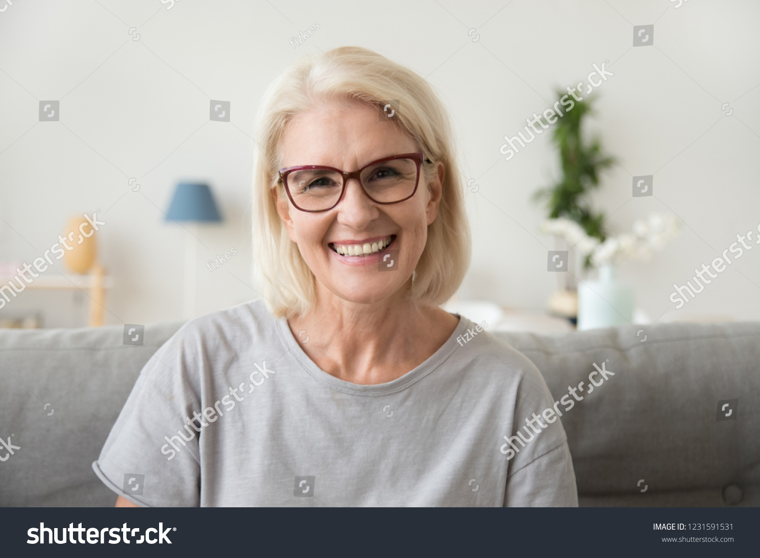 Smiling middle aged mature grey haired woman looking at camera, happy old lady in glasses posing at home indoor, positive single senior retired female sitting on sofa in living room headshot portrait #1231591531