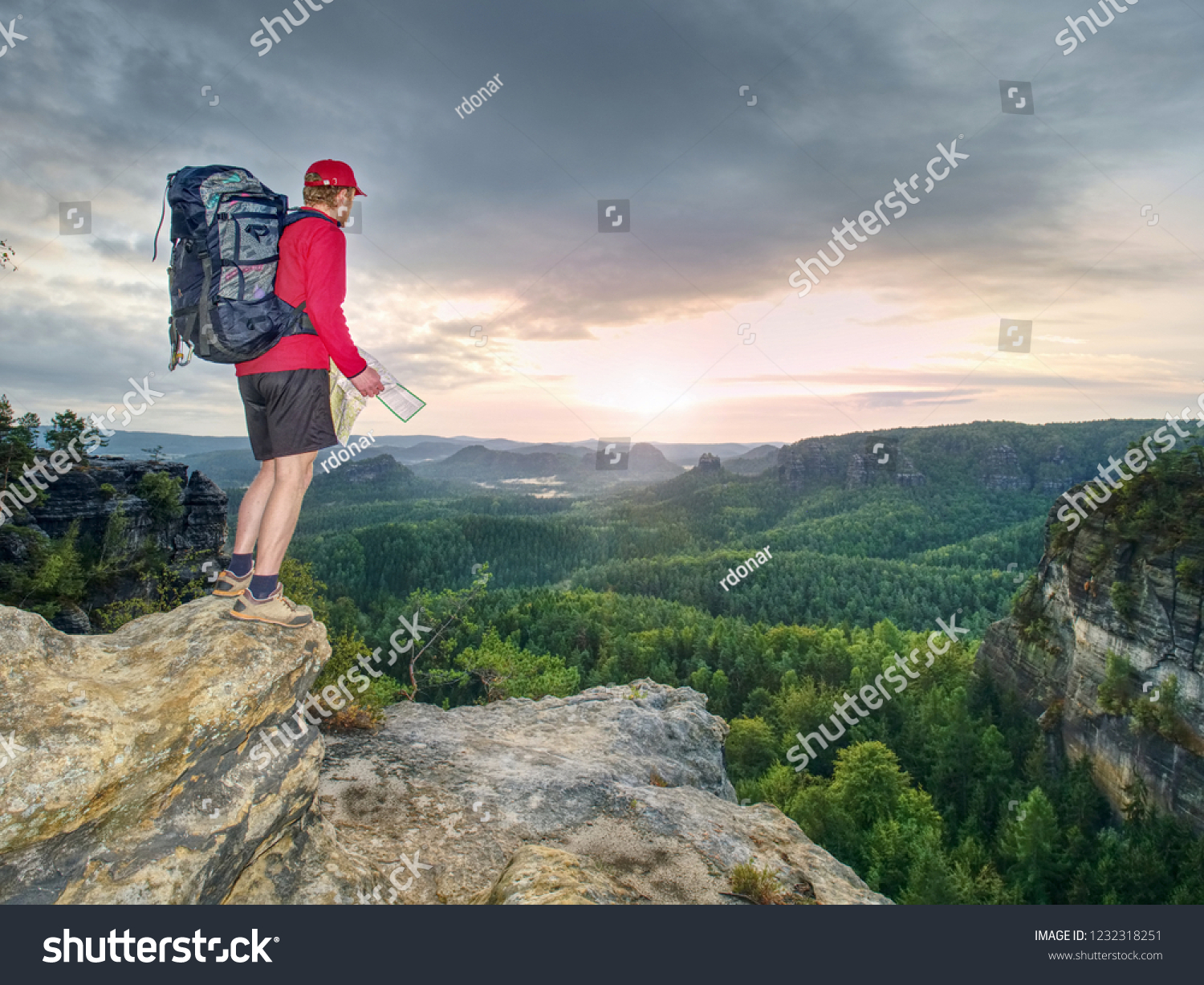 d5653d2bf780 Tall tourist with big backpack looking in paper map. Wild hilly nature  park. Hiker
