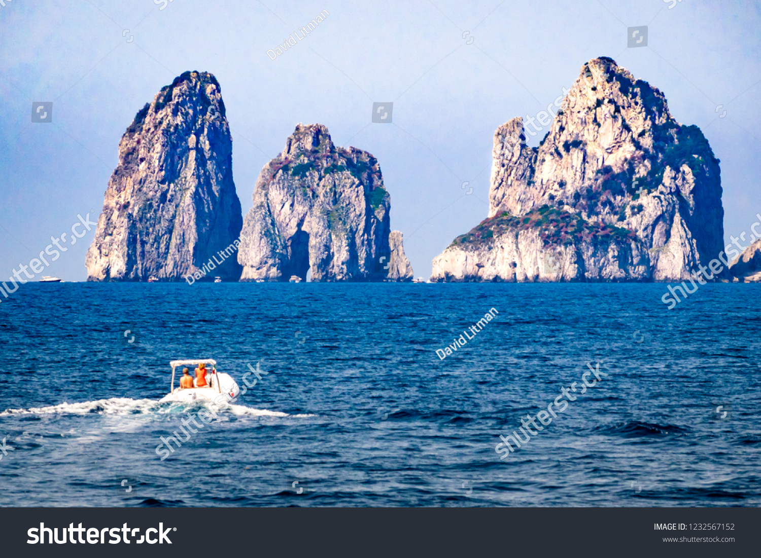 "Unidentifiable boaters  approach the three rocky ""stacks"" off the island of Capri in Italy, known as  I Faraglioni."