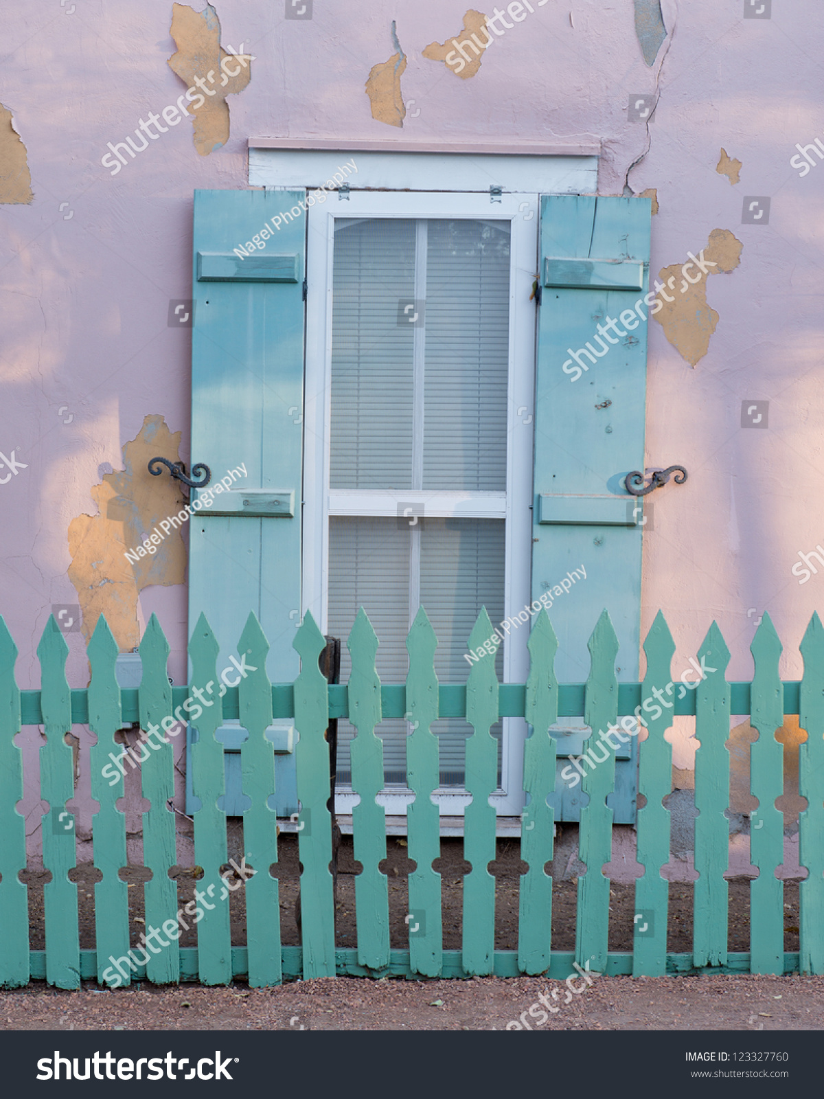 matching green picket fence window shutters stock photo