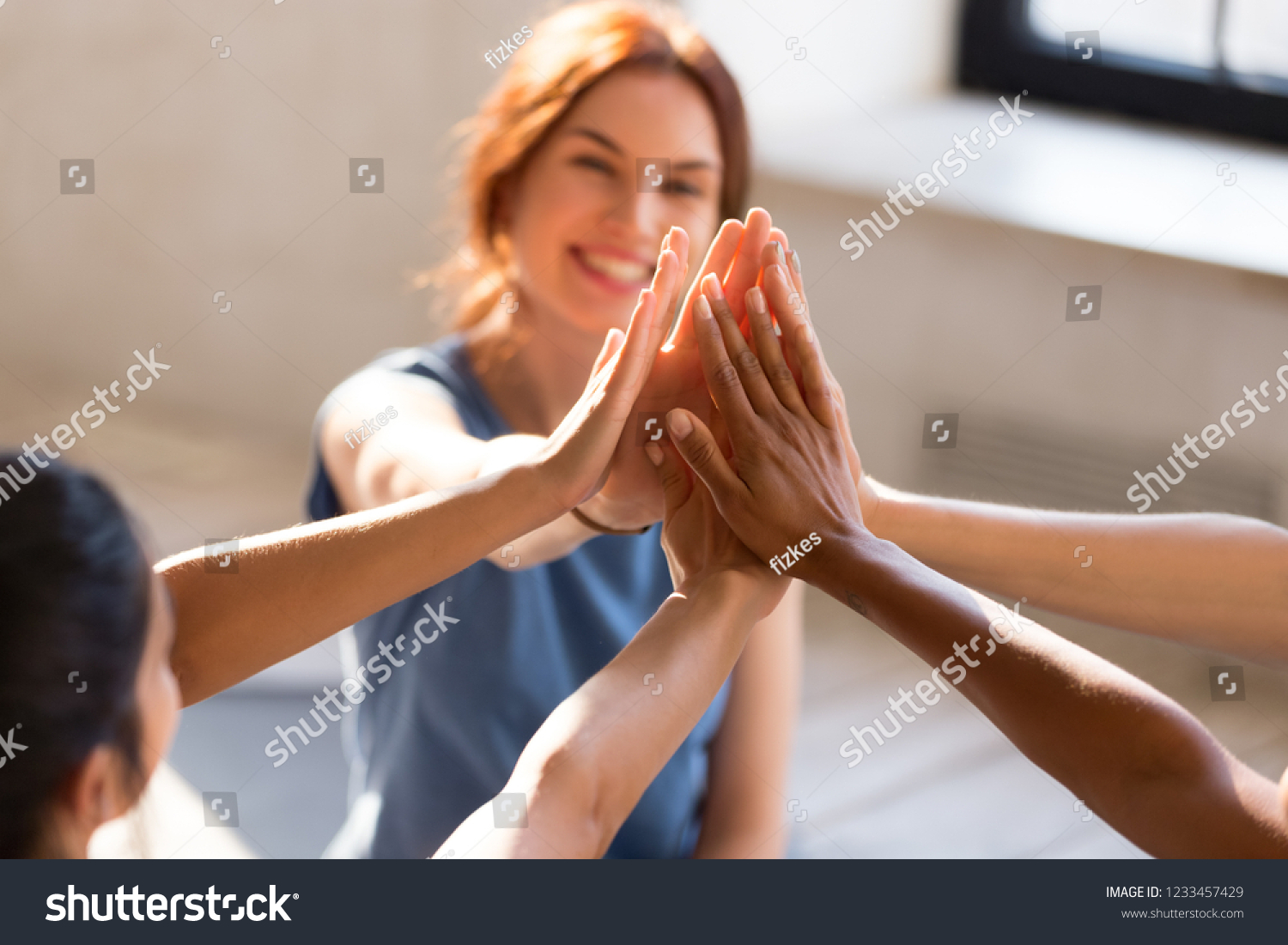 Cheerful diverse young girls sitting together in sports studio before starts training giving high five feel happy and healthy, close up focus on hands. Respect and trust, celebration and amity concept #1233457429