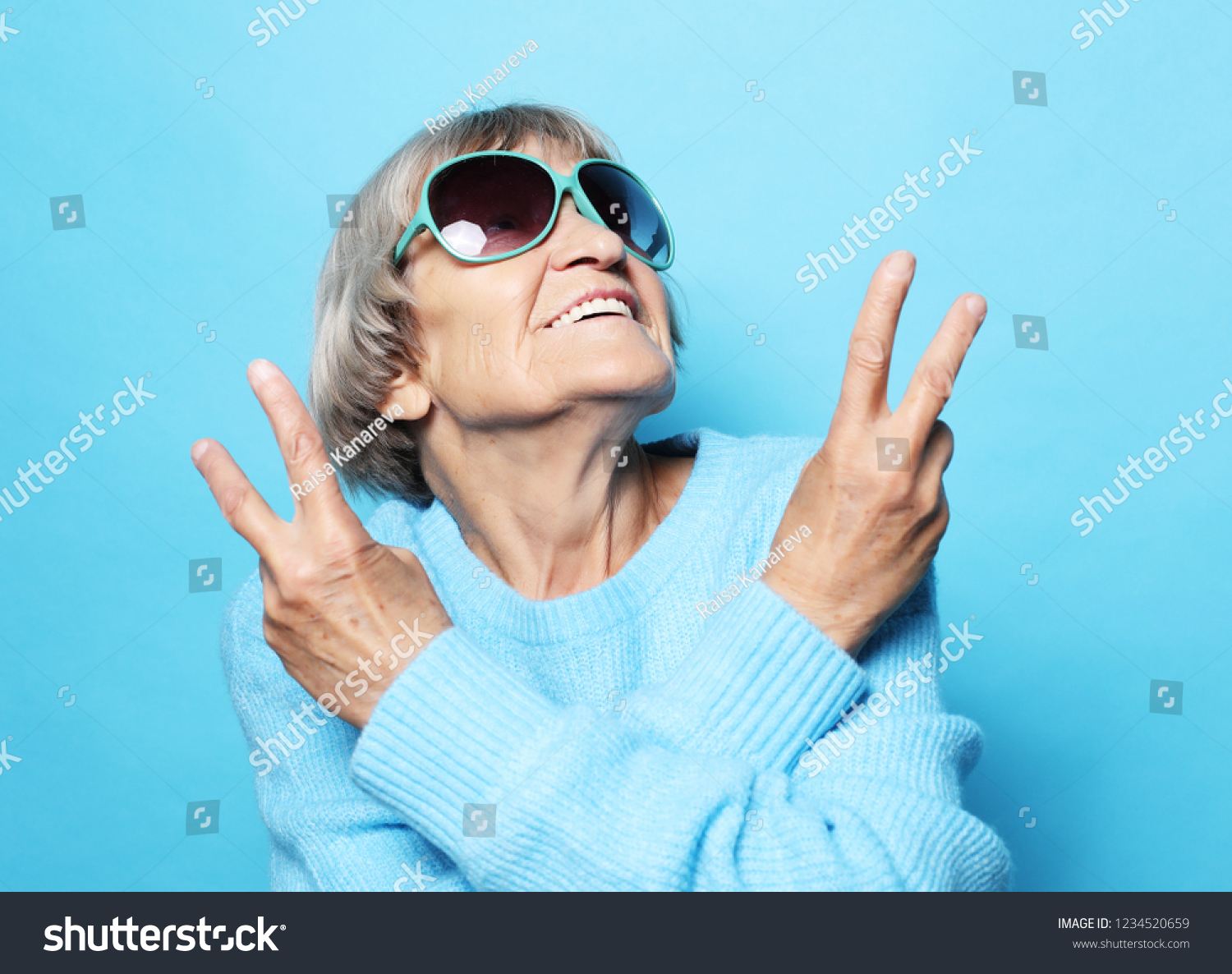 Lifestyle, emotion  and people concept: Funny old lady wearing blue sweater, hat and sunglasses showing victory sign. Isolated on blue background. #1234520659
