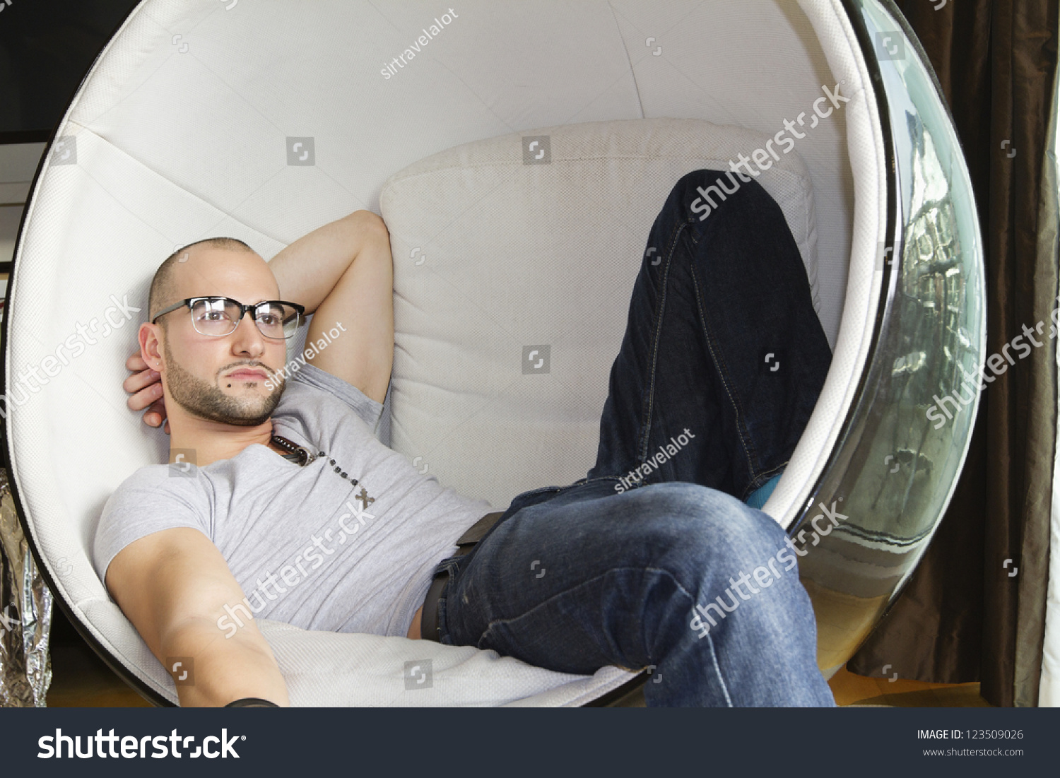 Thoughtful Man Sitting In A Round Egg Chair