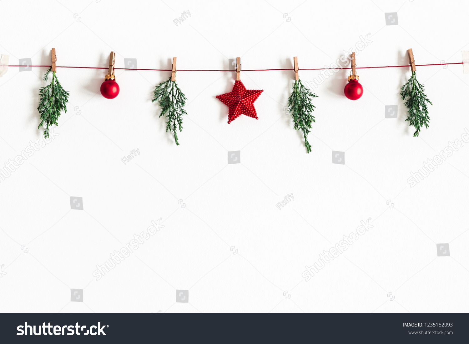 Christmas composition. Garland made of red balls and fir tree branches on white background. Christmas, winter, new year concept. Flat lay, top view, copy space #1235152093