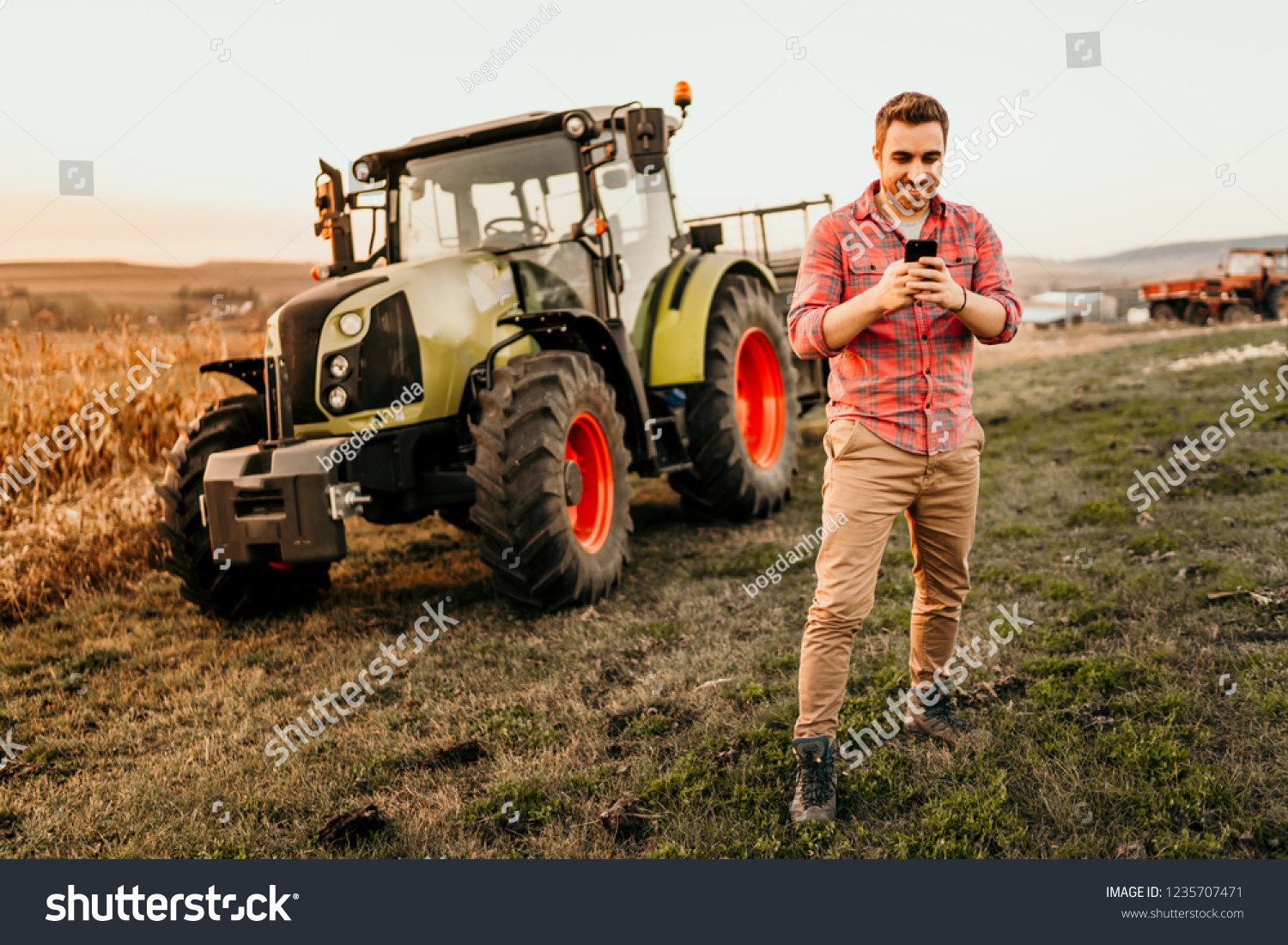 Farmer working on field using smartphone in modern agriculture - tractor  and trailer background