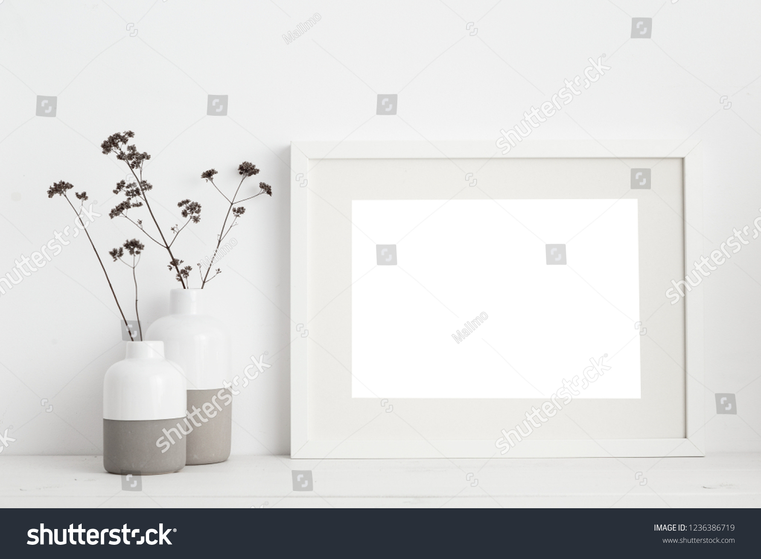 white frame mock up and dry twigs in vase on book shelf or desk. White colors.   #1236386719