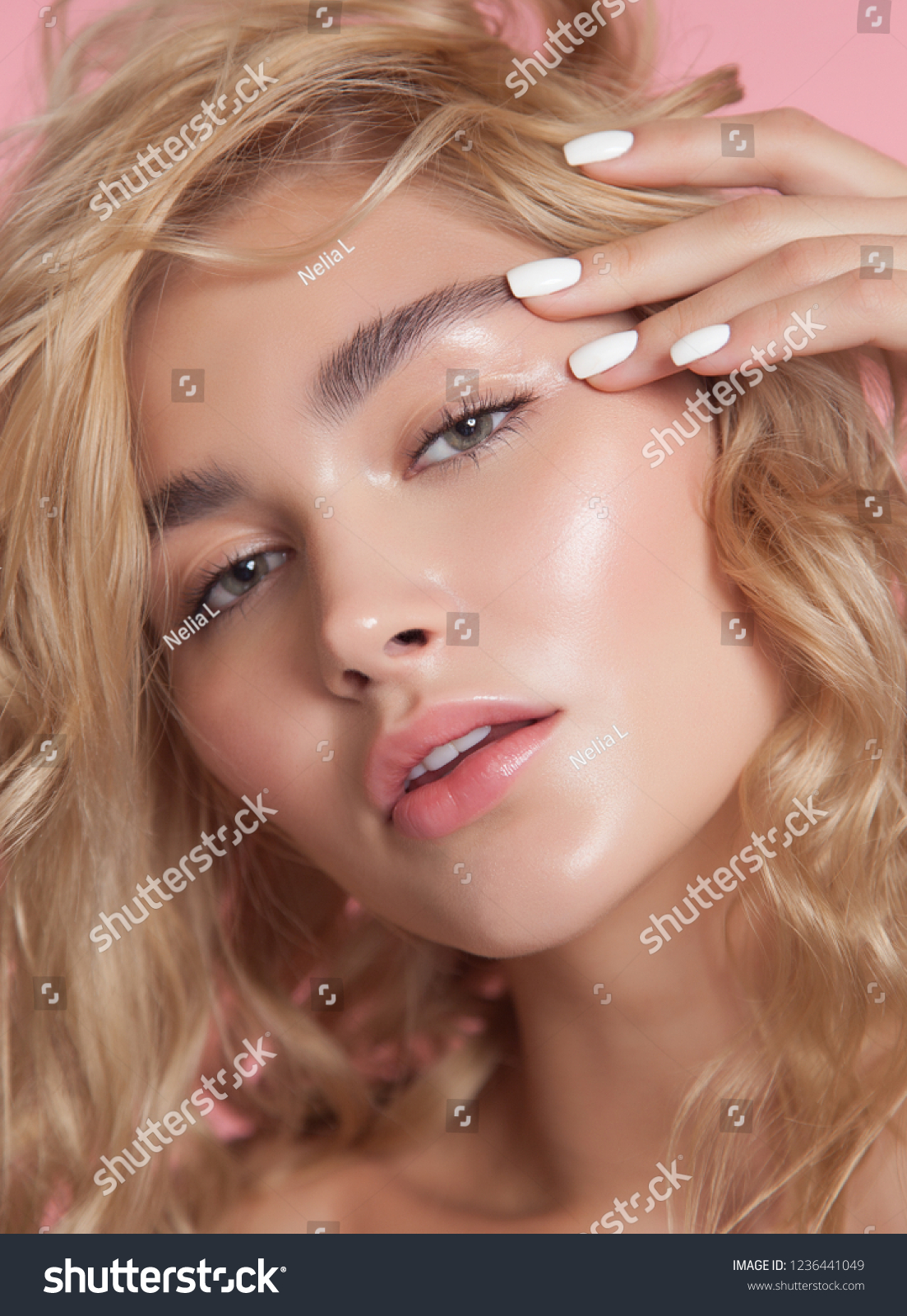 close-up beauty portrait. young model with glowing healthy skin. beautiful blonde woman with natural make-up. white nail laquer