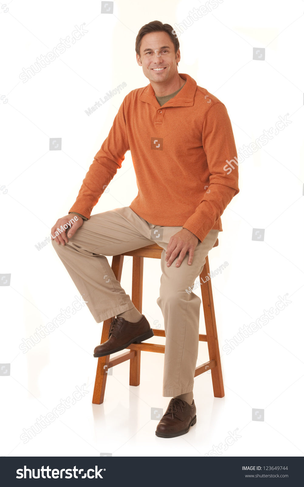 Portrait Of A Handsome Man Wearing An Orange Sweater Sitting On A Stool Isolated On A White