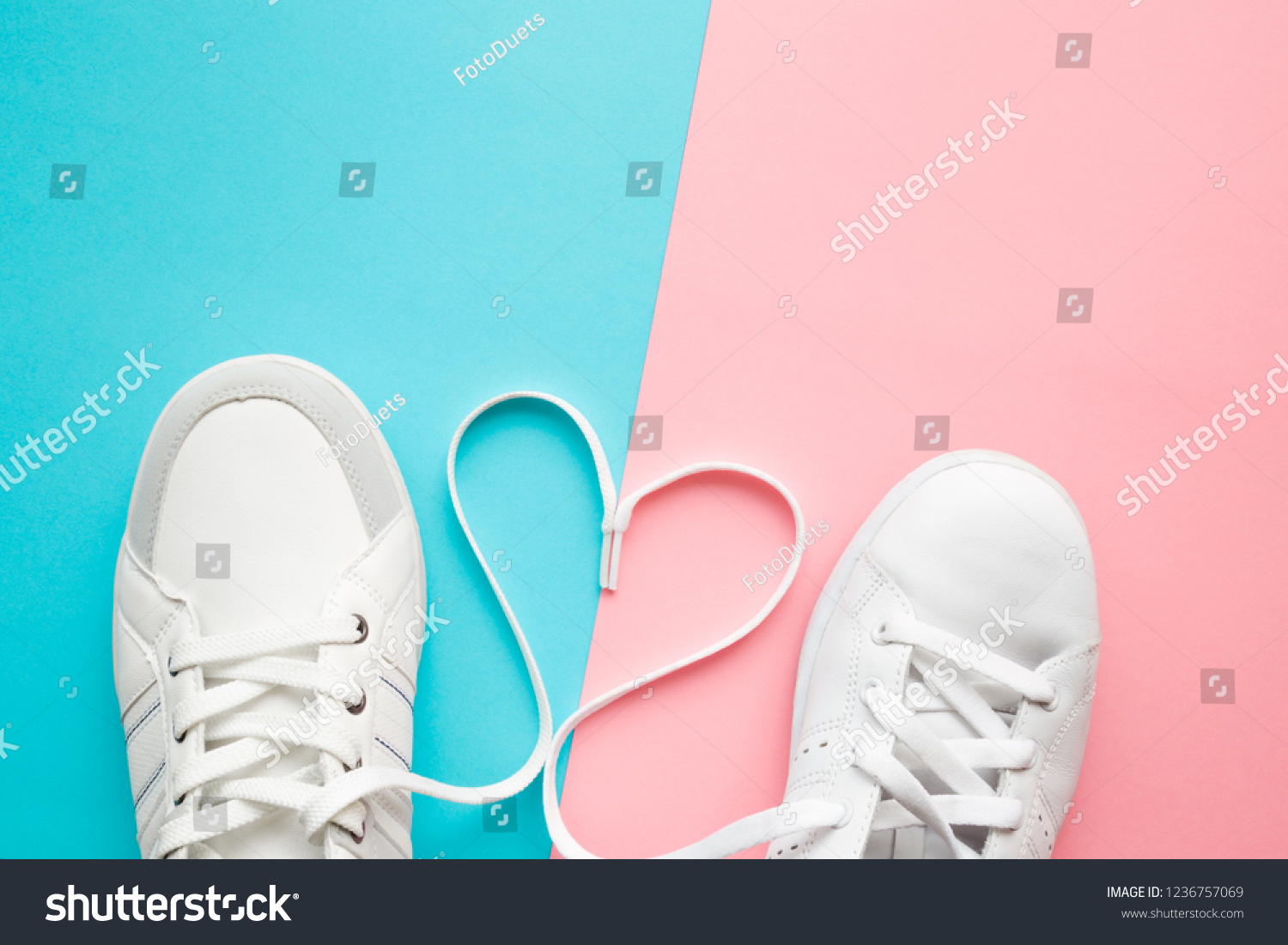Heart created from white shoelaces between male and female sport shoes. Love concept. Top view. Empty place for lovely, cute text, quote or sayings on pastel blue and pink paper background. Closeup. #1236757069