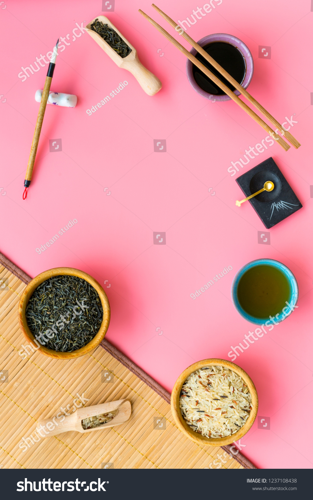 Chinese traditional symbols concept. Tea, rice, hieroglyph symbol, bambootabe mat, chopsticks, soy sause on pink background top view frame copy space #1237108438