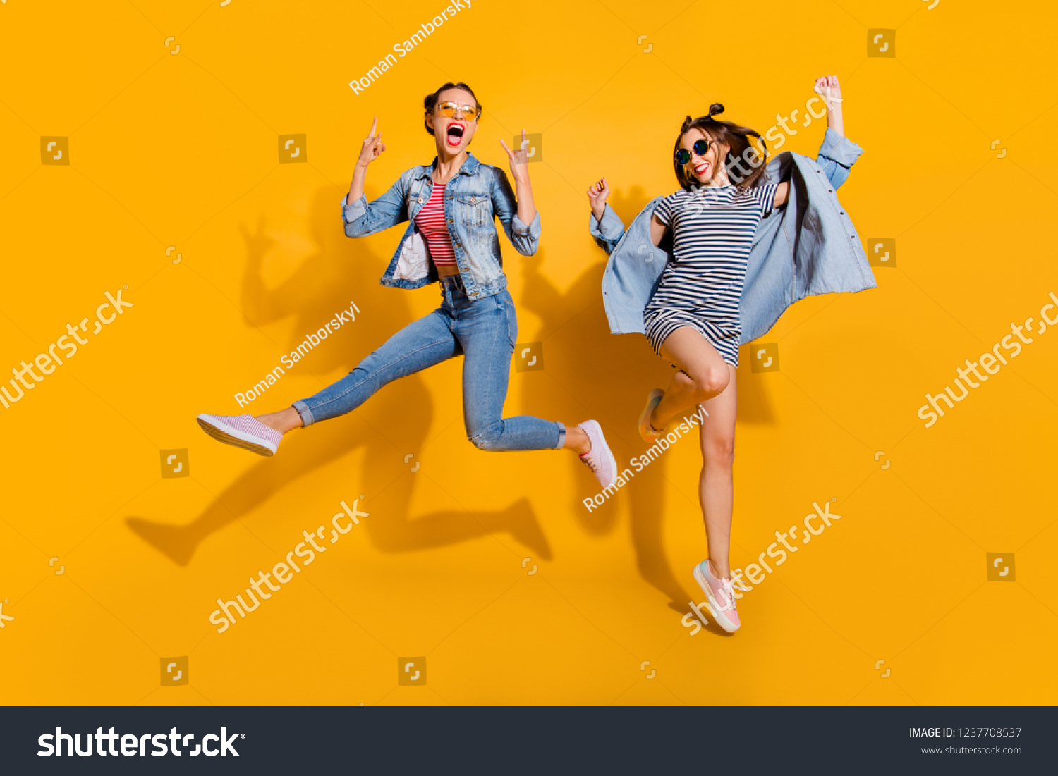Full legs body size two attractive music lover leisure lifestyle cool lady isolated on yellow vivid background in glasses spectacles dance dancer on concert raised fists up give heavy metal gesture #1237708537