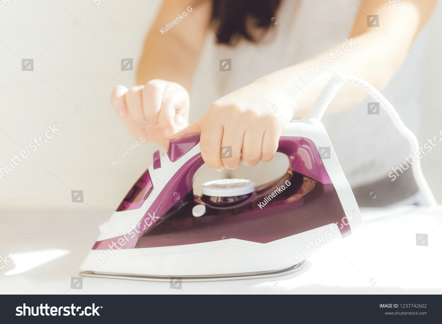 A young woman is ironing the shirt on the ironing board at home. Focus on hand and shirt's button.girl's hands iron clothes iron #1237742602