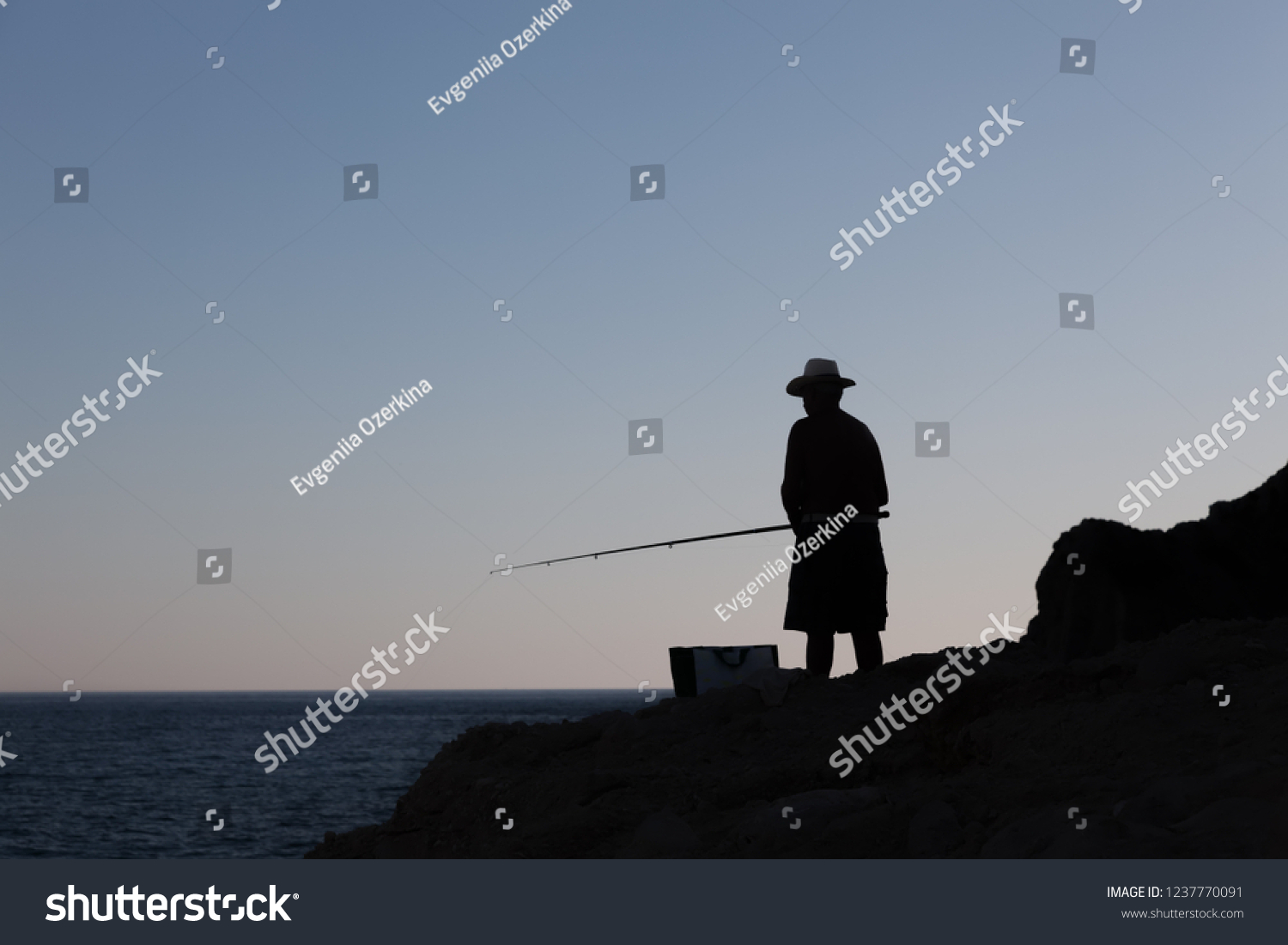 stock-photo-silhouette-of-a-fisherman-on
