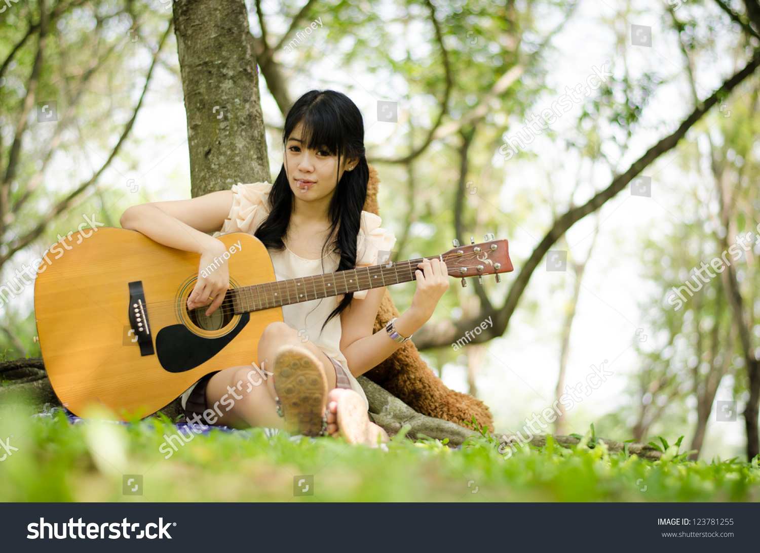 asian girl playing guitar under a tree in the garden