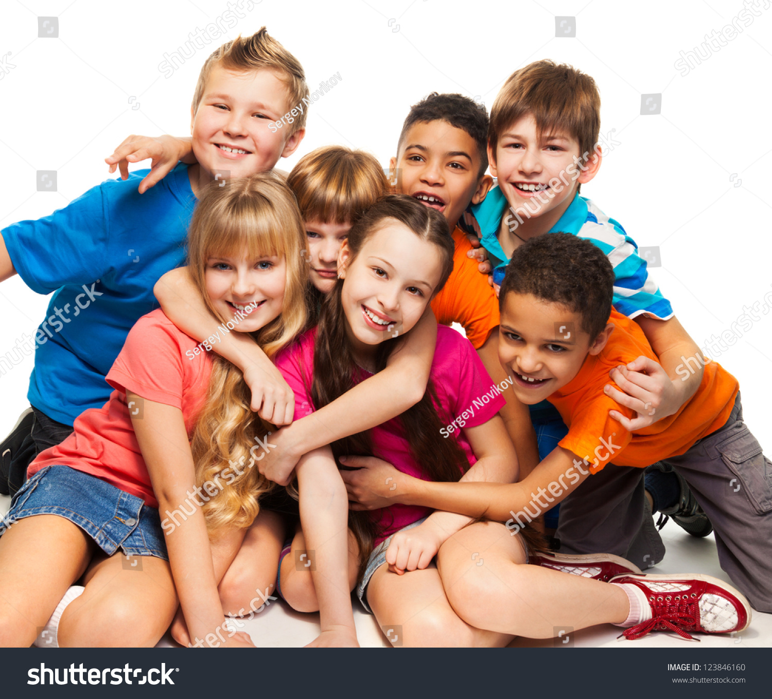 Group of happy smiling kids sitting together and playing boys and girls black and caucasian