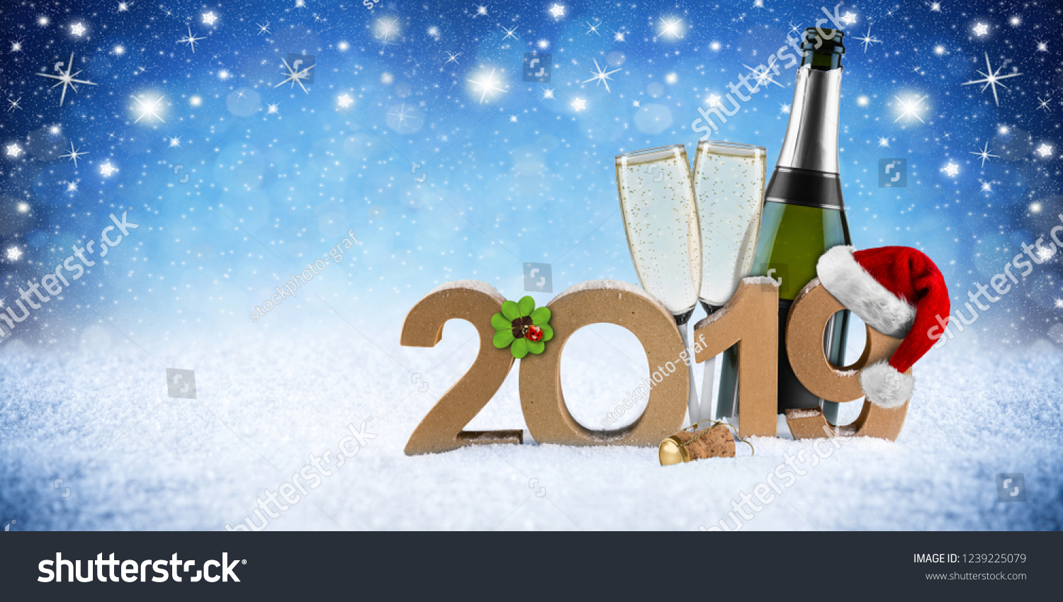 happy new year 2019 number with santa hat four leaf clover champagne bottle glass in front of blue snow night sky panorama background #1239225079