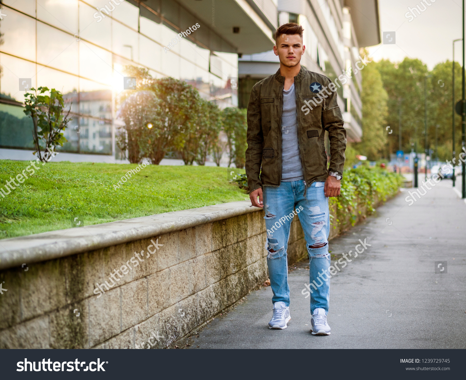 d67aa532 Handsome young man walking in city with backpack on shoulders, wearing t- shirt
