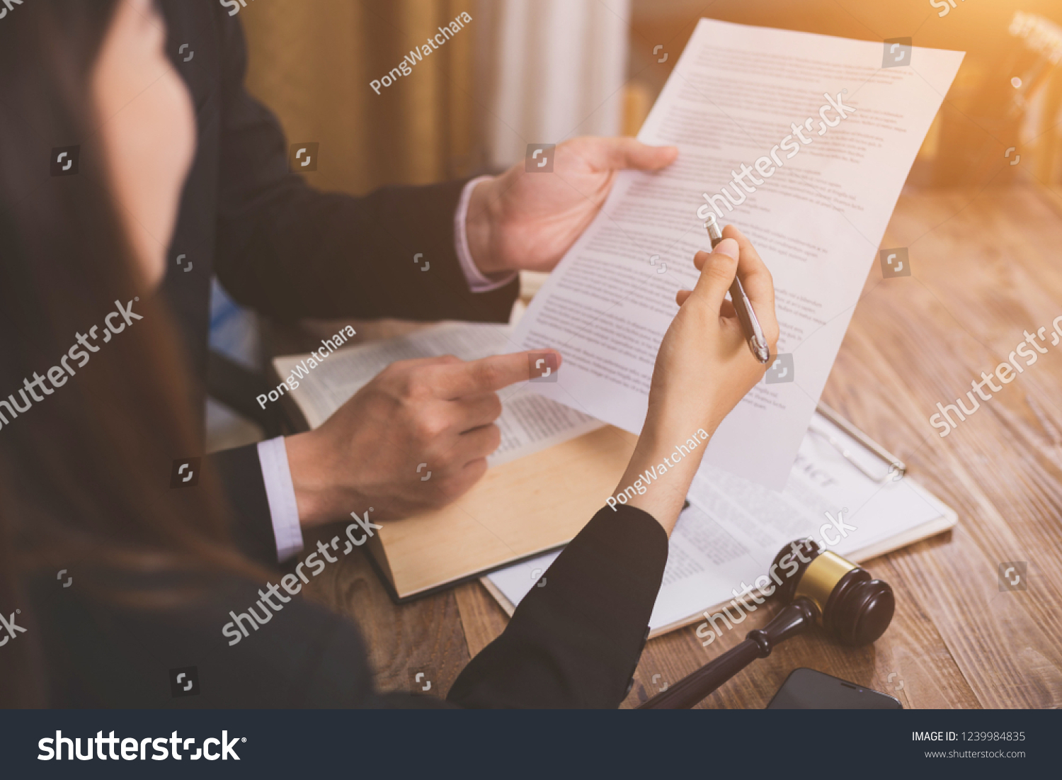 The hard work of an asian lawyer in a lawyer's office. Counseling and giving advice and prosecutions about the invasion of space between private and government officials to find a fair settlement. #1239984835