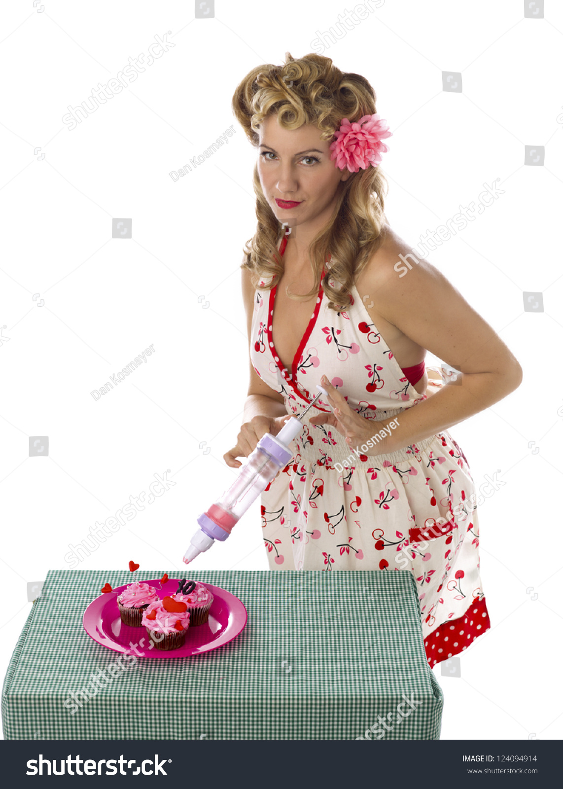 portrait of a beautiful young woman decorating cupcakes with whipped cream against white background