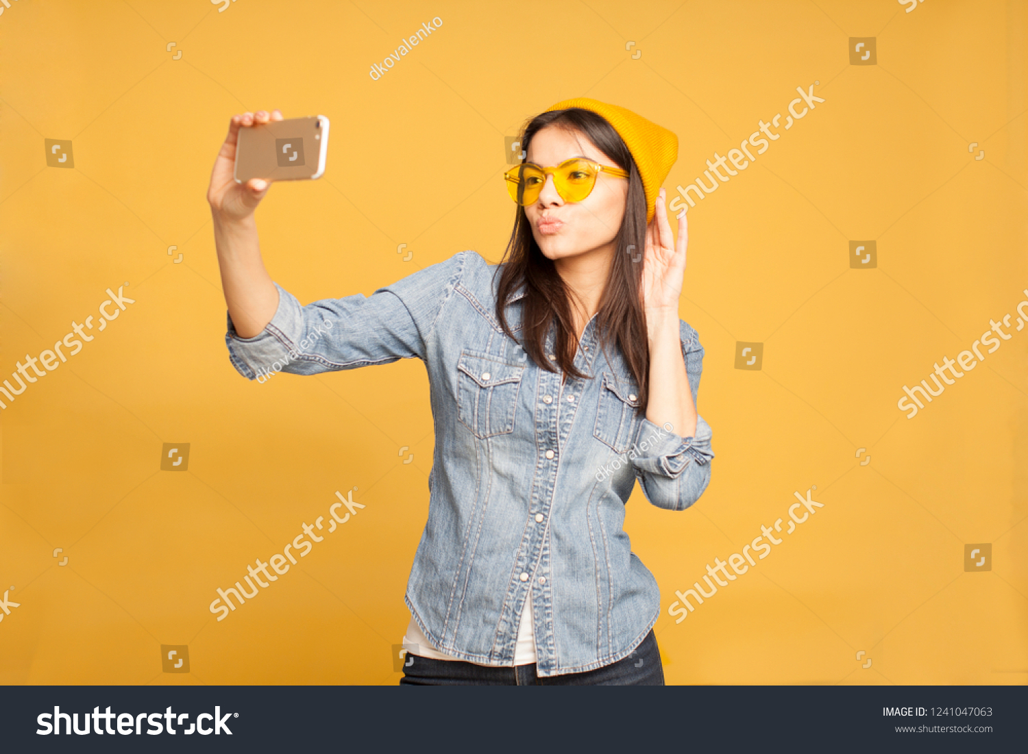 e12842df13 Portrait of happy beautiful young woman taking selfie on her phone and  smiling