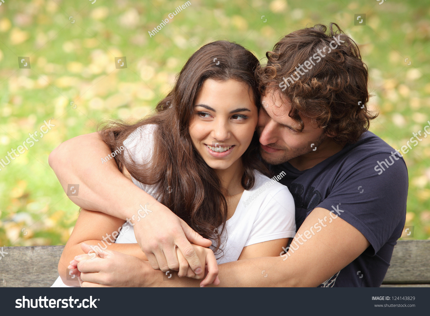 Pretty couple hugging and flirting in an urban park sitting in a bench and  looking away. Pretty Couple Hugging Flirting Urban Park Stock Photo 124143829