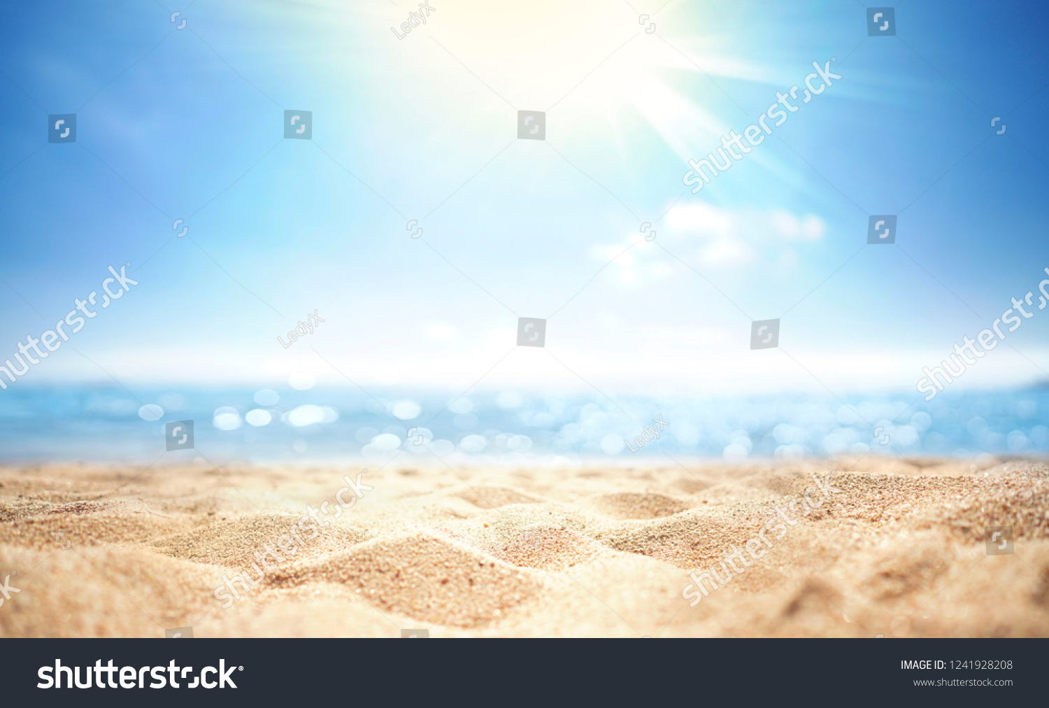 Abstract blur defocused background, nature of tropical summer beach with rays of sun light. Golden sand beach, sea water against blue sky with white clouds. Copy space, summer vacation concept. #1241928208
