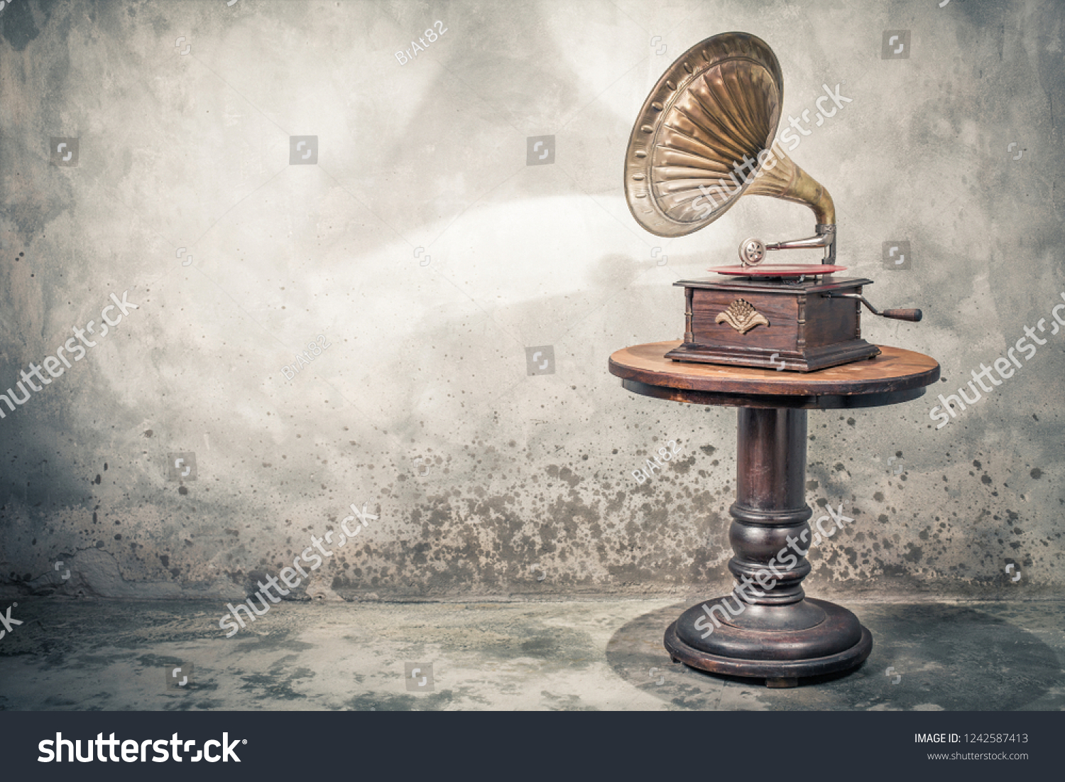 Vintage antique gramophone phonograph turntable with brass horn and red color vinyl disc record on wooden table front concrete wall background with shadow. Retro old style filtered photo #1242587413