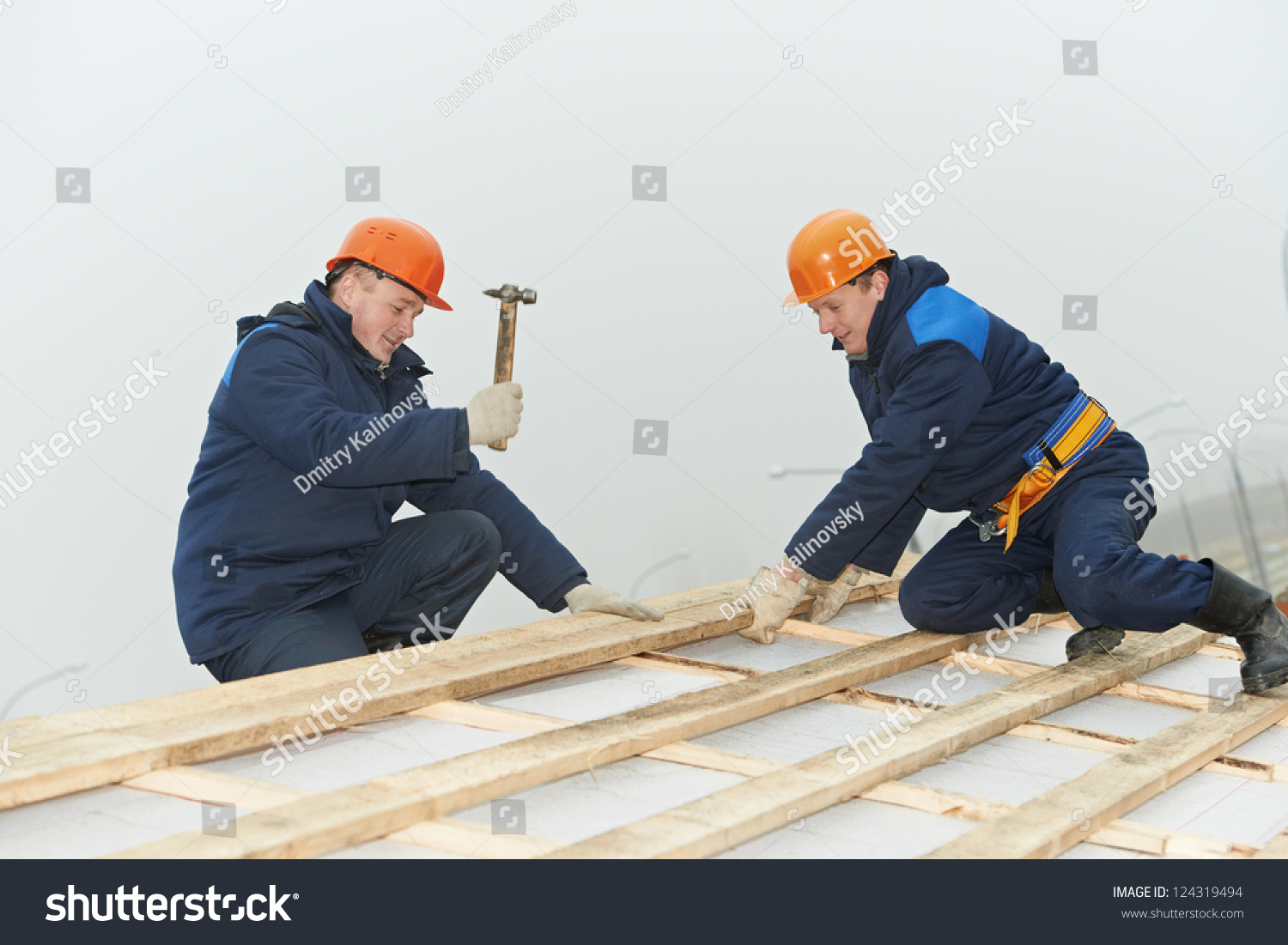 two roofers nailing wood roof boarding lathing with hammer stock photo 124319494 shutterstock. Black Bedroom Furniture Sets. Home Design Ideas