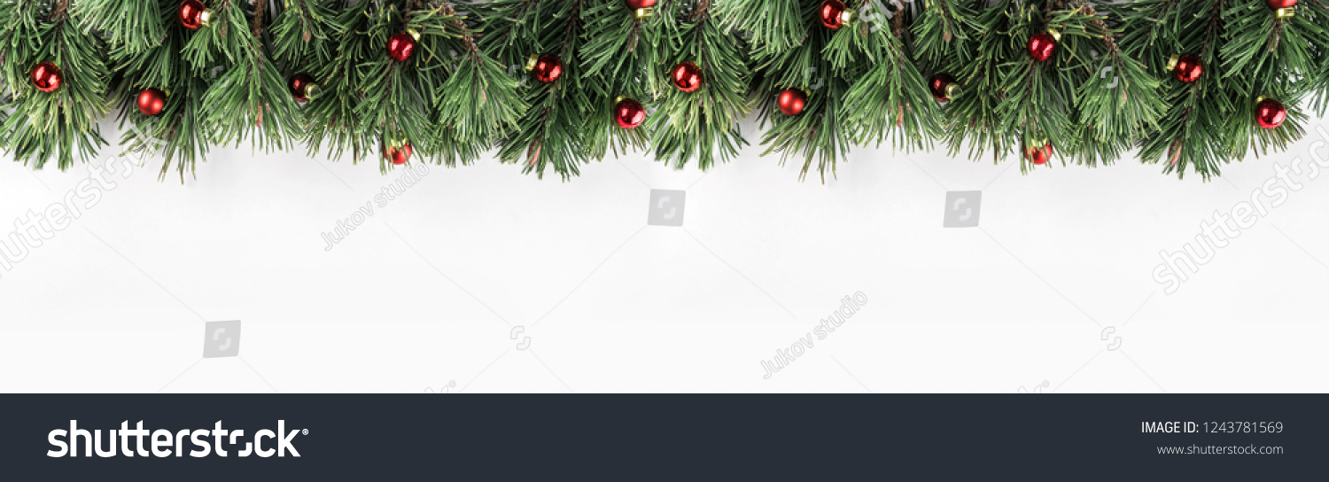 Christmas garland of Fir branches with red decoration on white background. Xmas and Happy New Year theme. Flat lay, top view, wide composition #1243781569