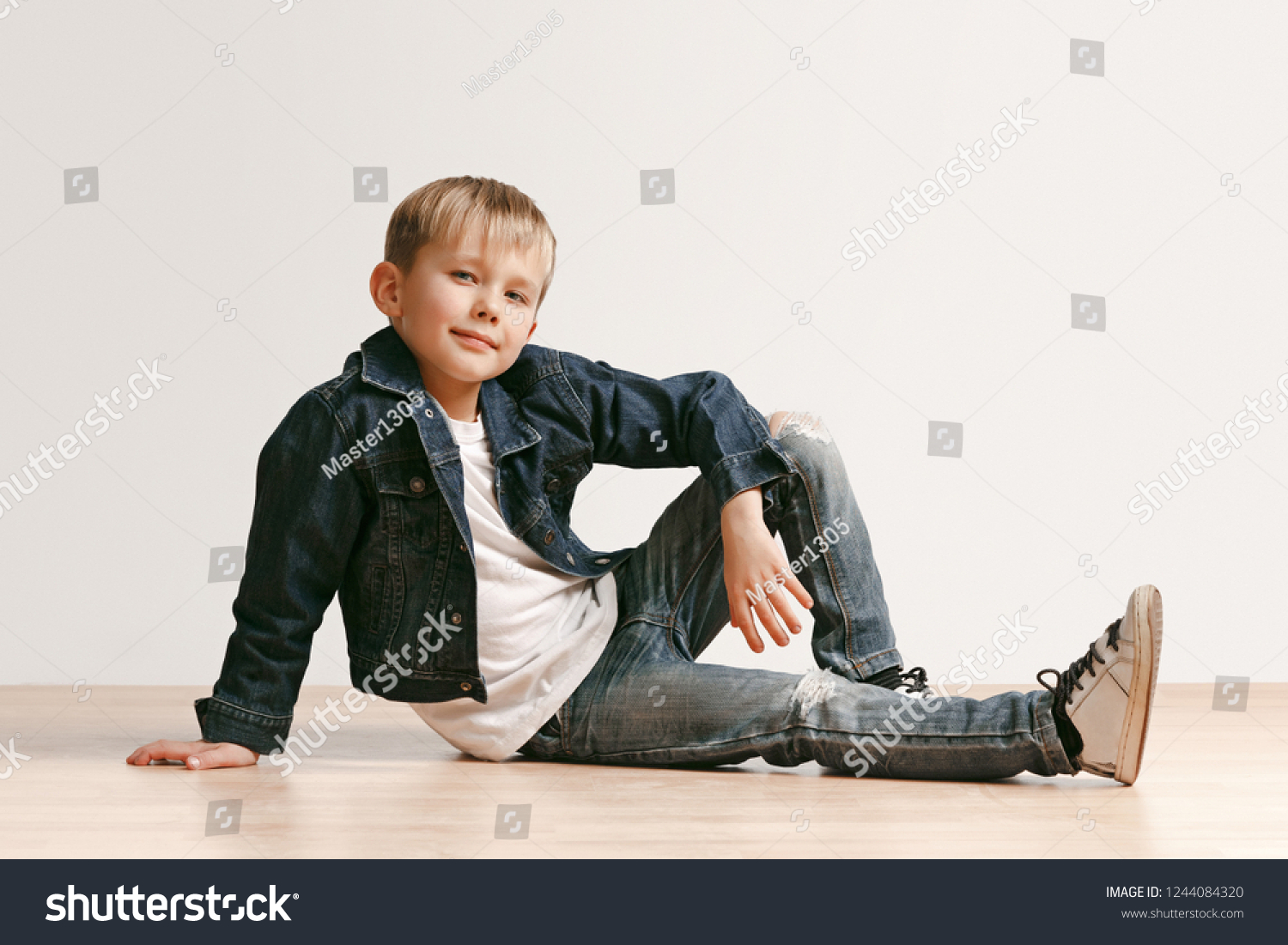 f94aa034f The portrait of cute little kid boy in stylish jeans clothes looking at  camera against white