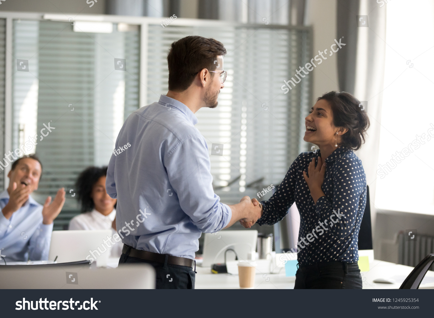 Team leader motivating handshaking female Indian excited employee, congratulate with promotion, business achievement, thank for good result, work, expressing respect, support, colleagues applaud #1245925354