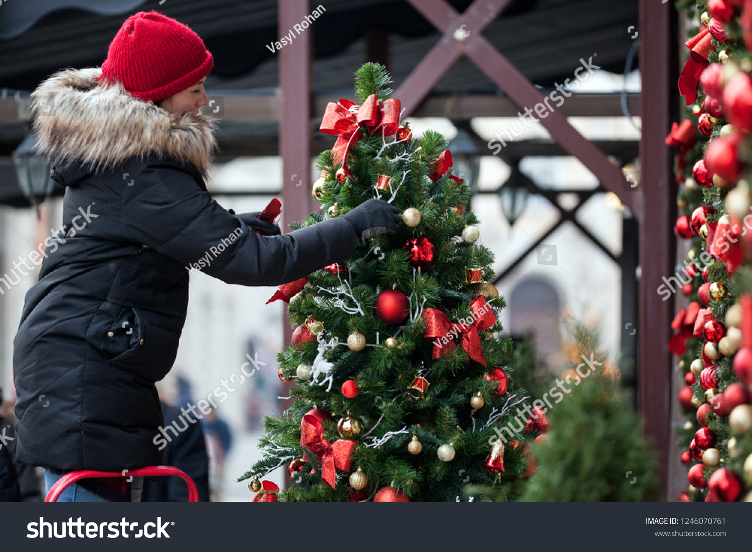 Decorating Christmas Trees Outside.Woman Decorating Christmas Tree Outside Outdoor Stock Photo