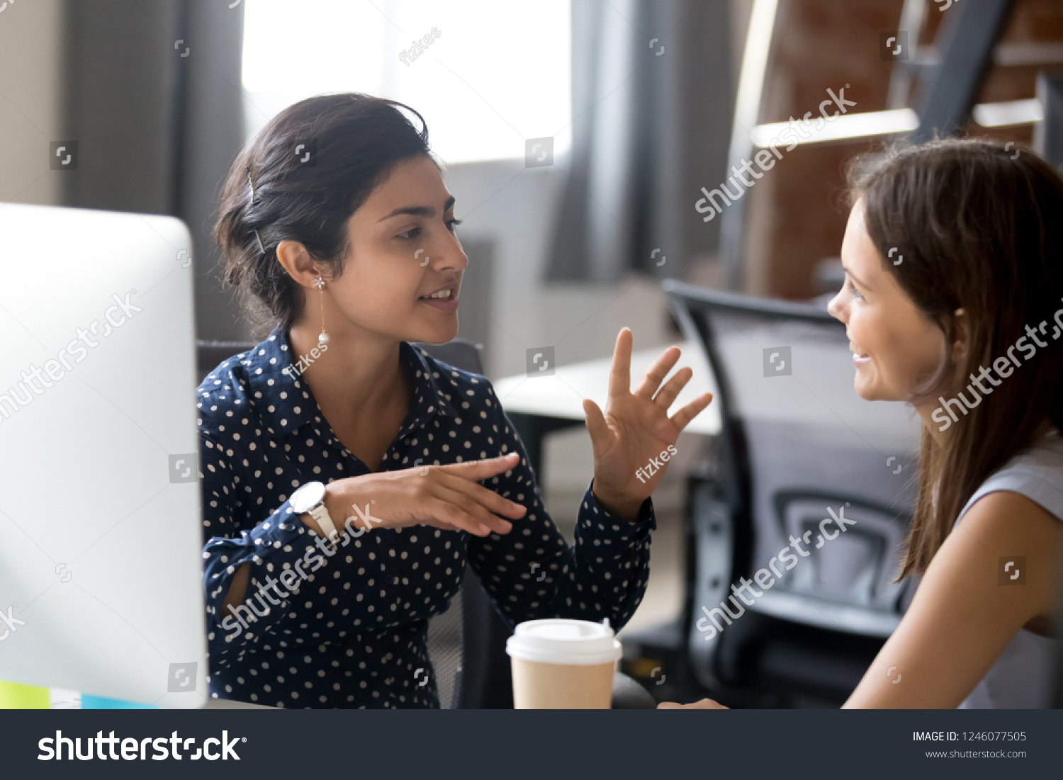 Friendly female colleagues having good relationships, pleasant conversation at workplace during coffee break, smiling young woman listen talkative coworker, discussing new project, talking in office #1246077505