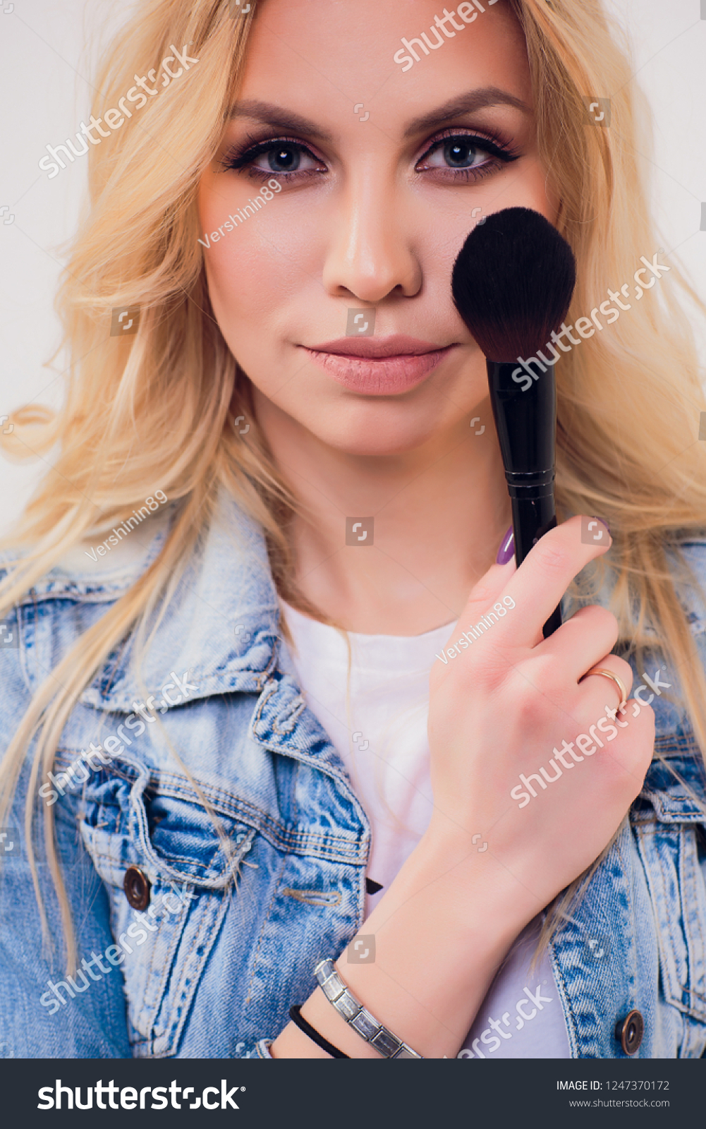 Beauty Woman with Makeup Brushes. Natural Make-up for Blonde Model Girl with Blue Eyes. Beautiful Face. Makeover. Perfect Skin. Applying Holiday Makeup with ...