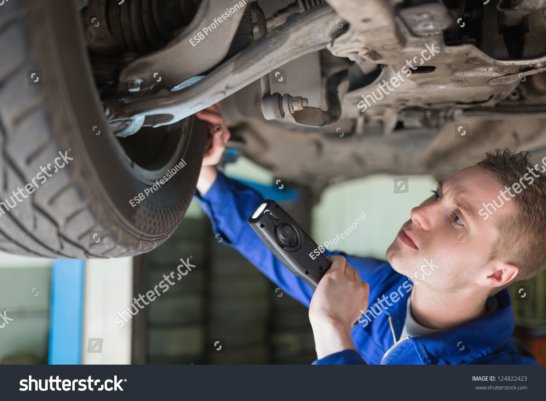 male mechanic flashlight examining tire stock photo edit now