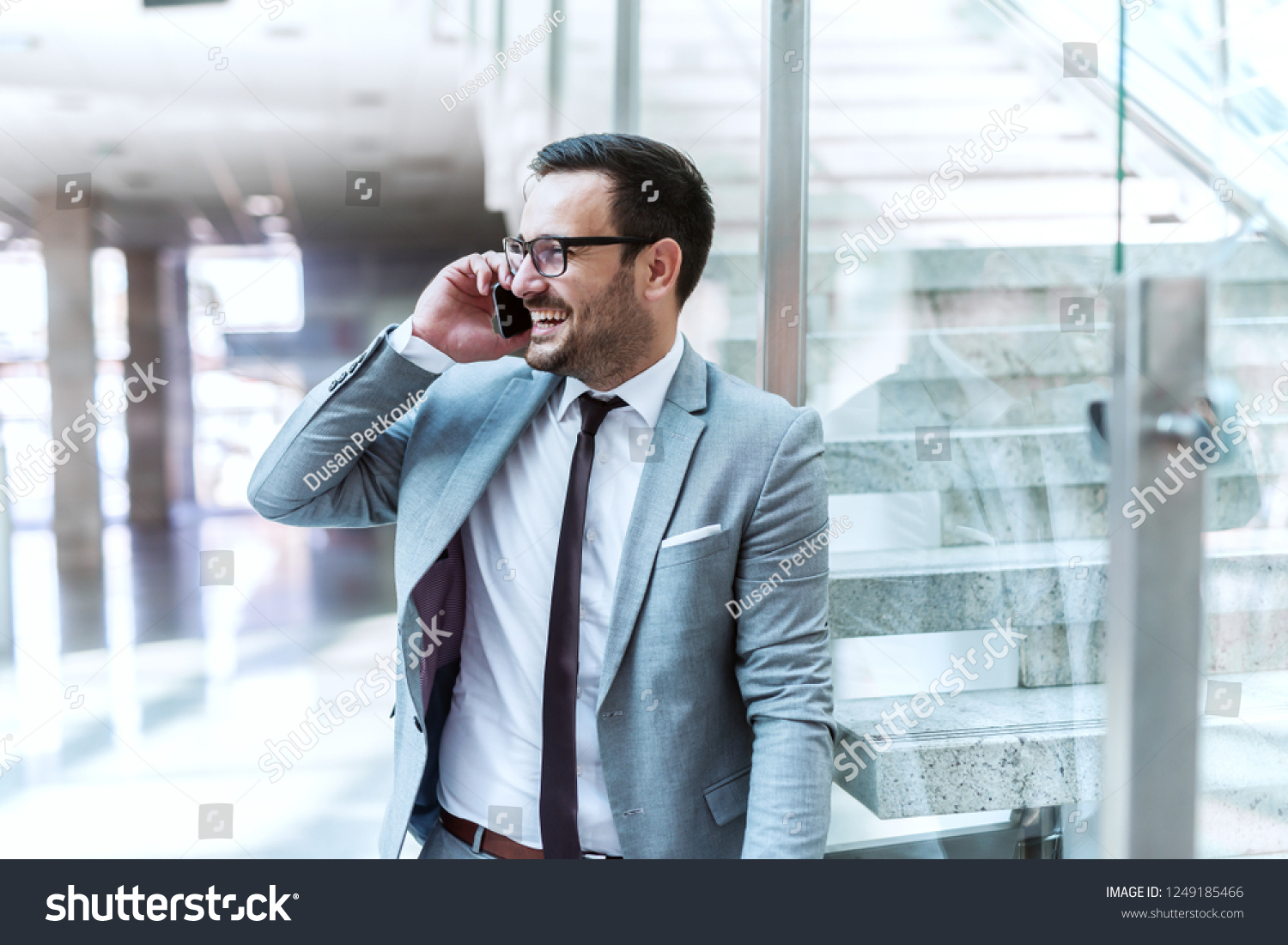 37ed7e96c9e6 Happy suited businessman using smart phone for business talk while leaning  on the glass.