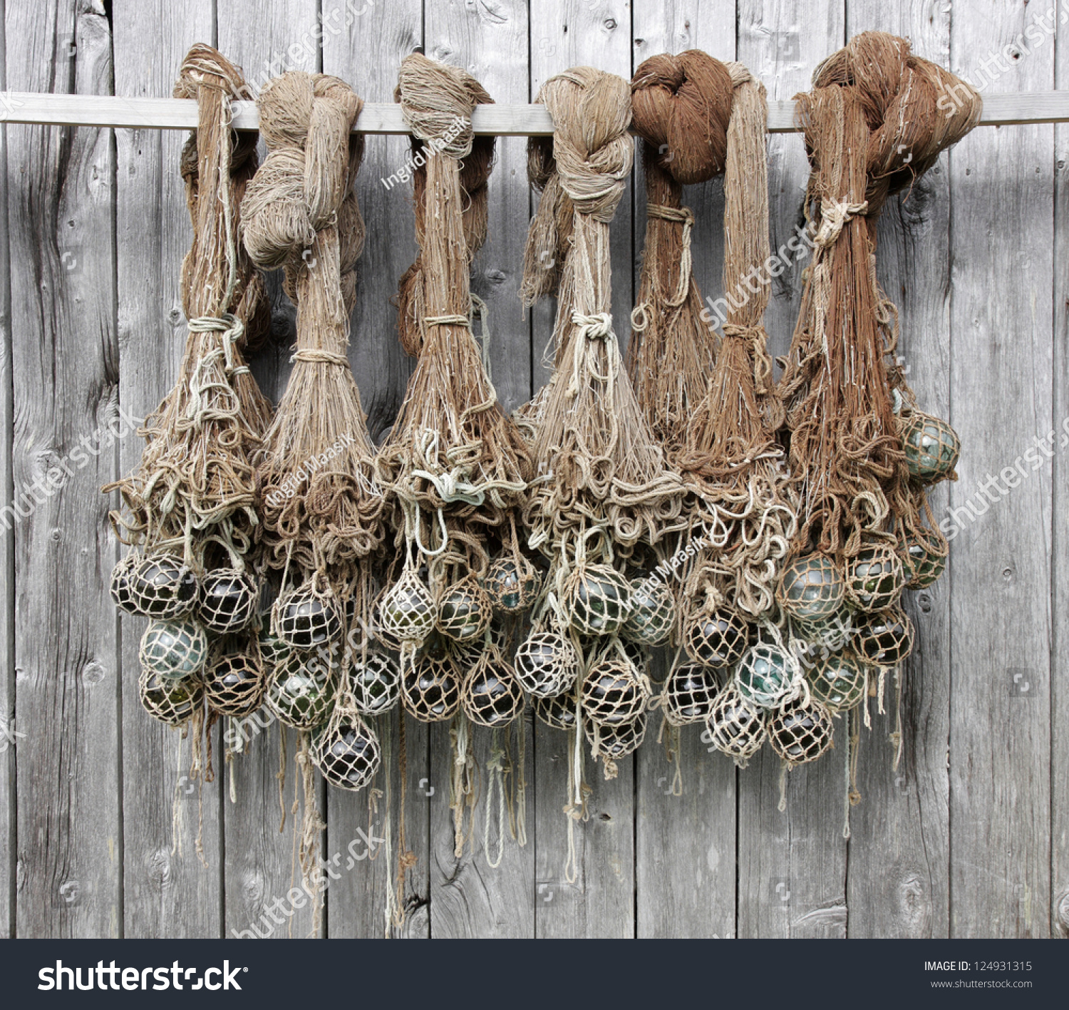 Old fishing nets with glass floats hanging at a boathouse for Fishing nets for sale