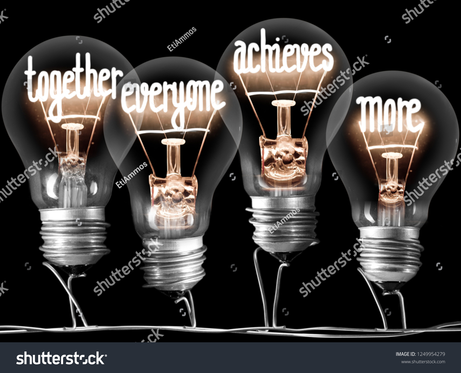 Photo of light bulbs with shining fibers in a shape of TOGETHER, EVERYONE, ACHIEVES, MORE concept words isolated on black background #1249954279