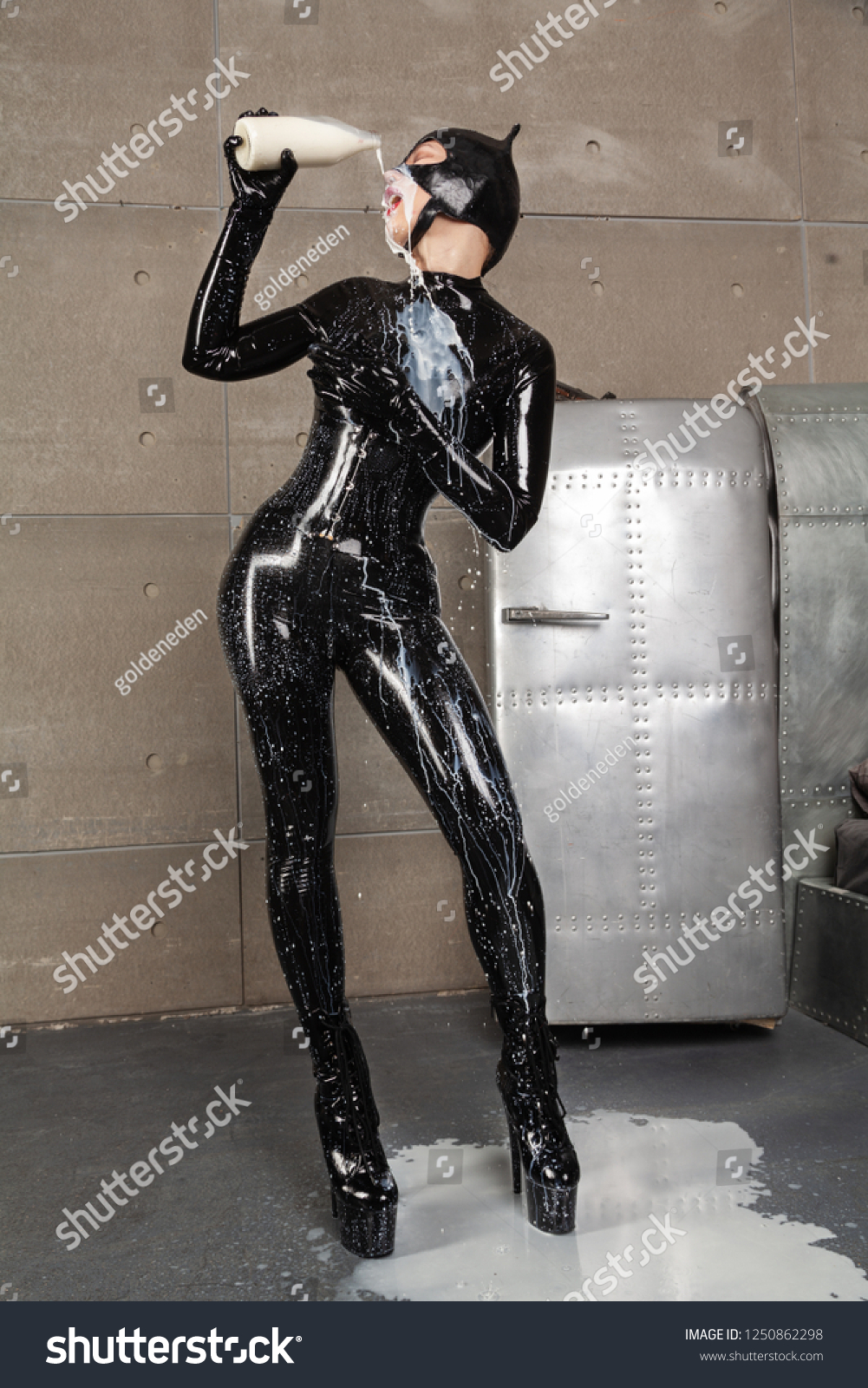 Pretty Woman Wearing Black Fetish Latex Rubber Catsuit With Tight Corset  and Cat Mask Playing With