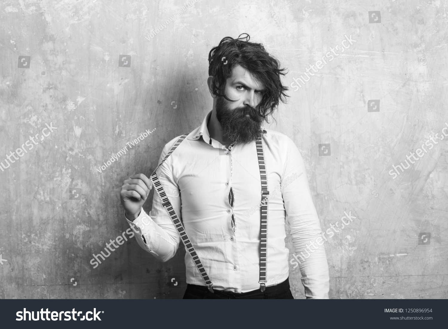 Business fashion and beauty. Fashion model with stylish hair. Guy or businessman at textured wall. Man with long beard and mustache on face. Hipster in shirt and suspenders. #1250896954