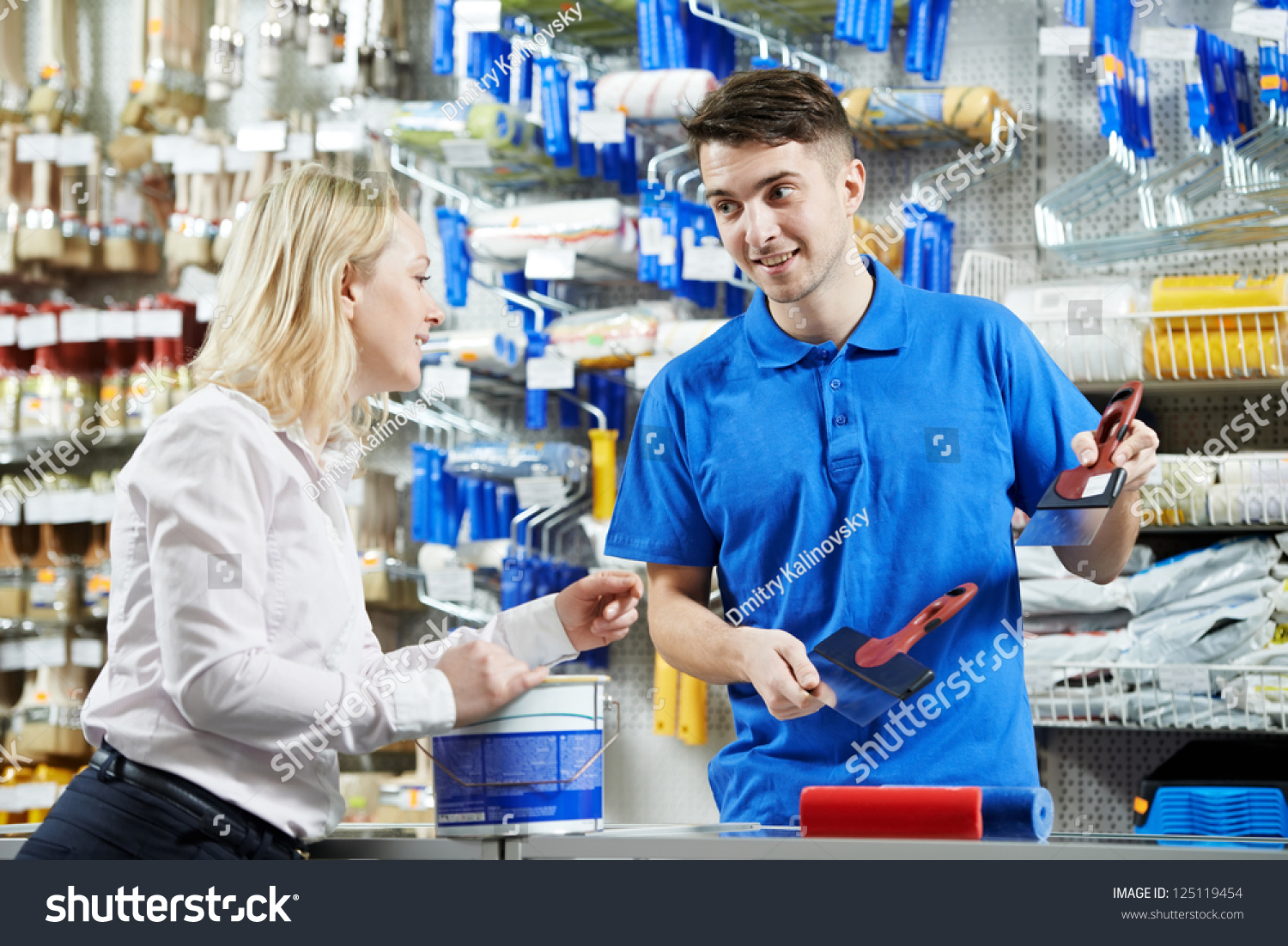 assistant seller help buyer by demonstrating stock photo  assistant seller help buyer by demonstrating putty knife for filling at hardware store