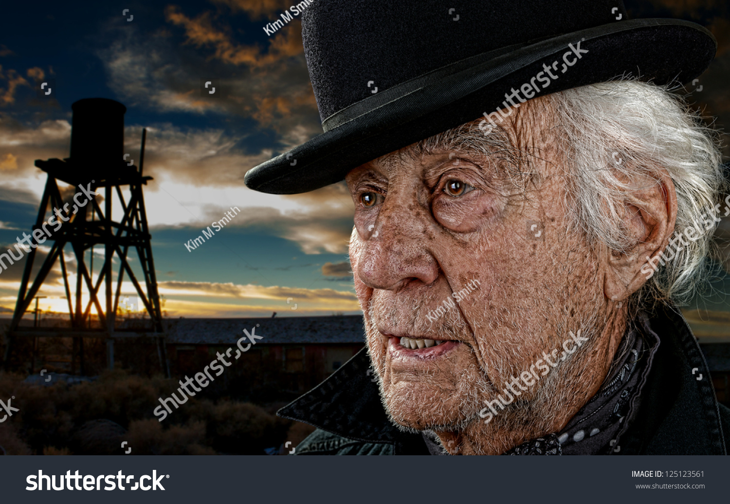 e7f24613f36 Old man wearing a black bowler hat with an old building and water tower  against a