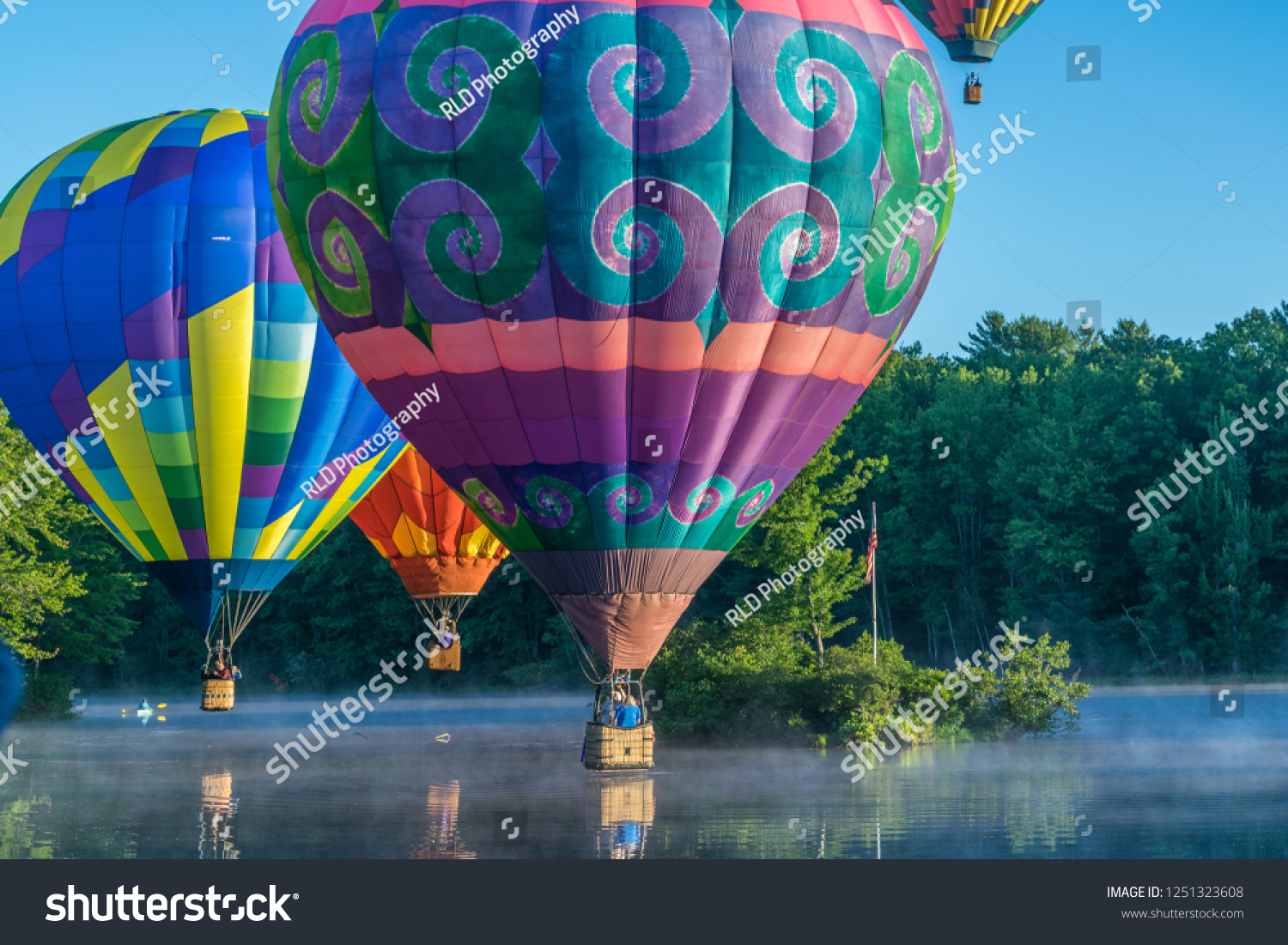 An image of hot air balloons performing skill maneuvers and an aerial ballet over an open body of water gently touching the surface and taking flight during a balloon rally.