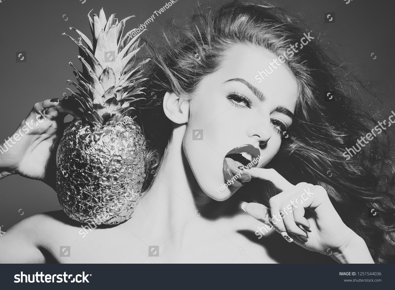 Sexy woman with finger in sensual mouth. Girl with golden pineapple or  ananas. Beauty