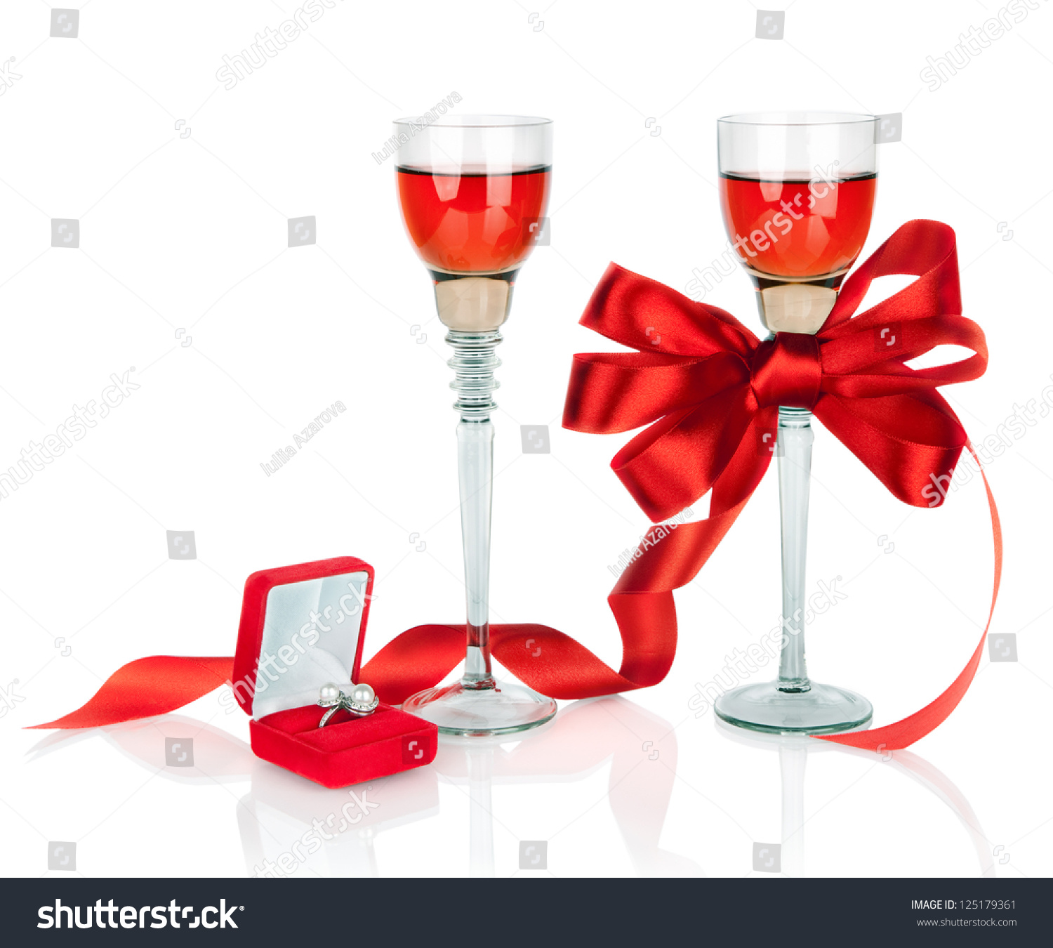 Wine in two wineglasses with red satin bow and wedding rings in gift ...