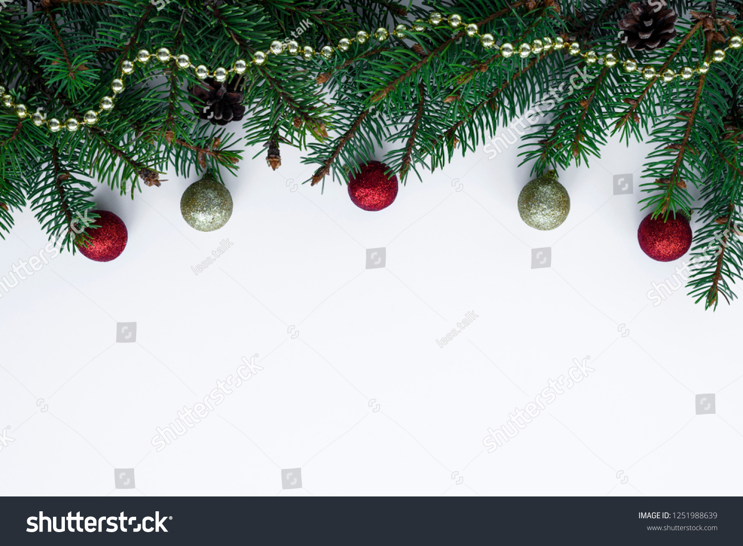 Decorative garland from christmas tree branches and cones. Top frame on white background, arranged from chain, little red and gold baubles. Copy space for wishes. #1251988639