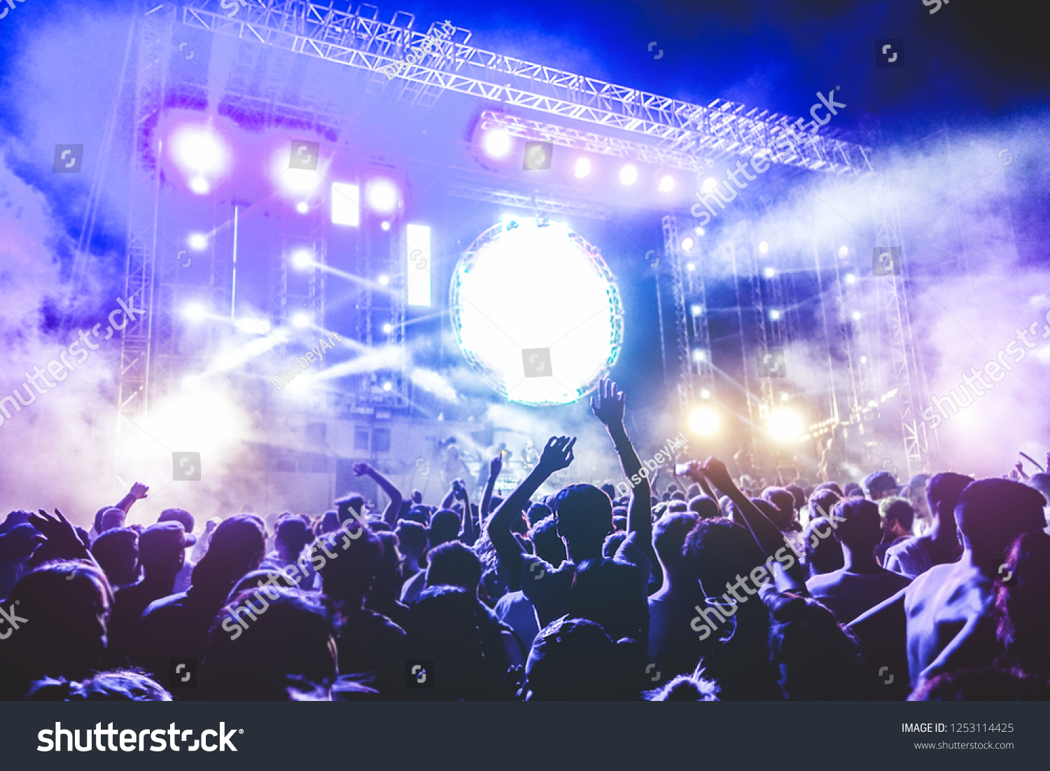 Happy people dancing and having fun in new year's eve festival party outdoor - Crowd of millennial guys celebrating concert event - Soft focus on center man head with hands up - Fun and youth concept #1253114425