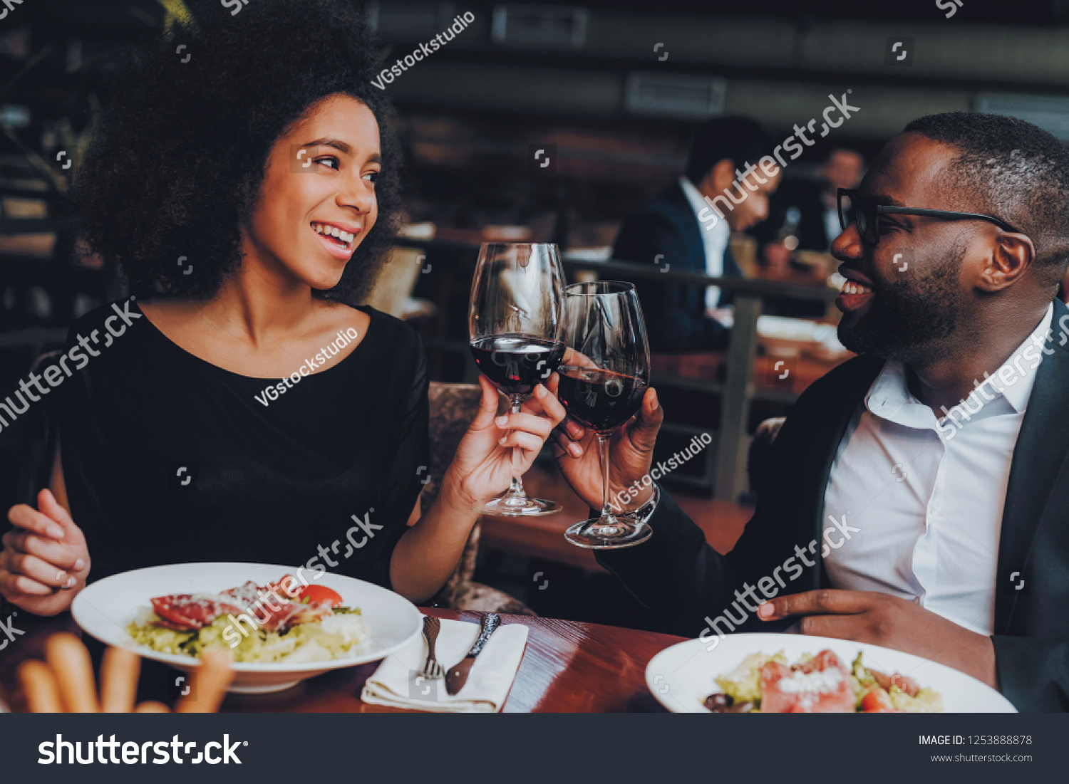 African American Couple Dating in Restaurant. Romantic Couple in Love Dating. Cheerful Man and Woman with Menu in a Restaurant Making Order. Romantic Concept. Cheers Classes Red Wine. #1253888878